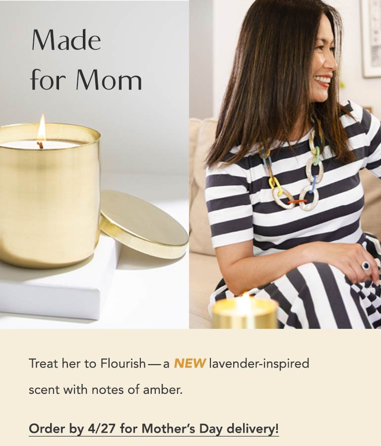 Made for Mom. A delightfully scented and handcrafted wax candle burns on a coffee table, while a mom and her son sit on a couch together on Mother's Day. Treat mom to Flourish - a new lavender-inspired scent with notes of amber. Order by 4/27 for Mother's Day delivery.