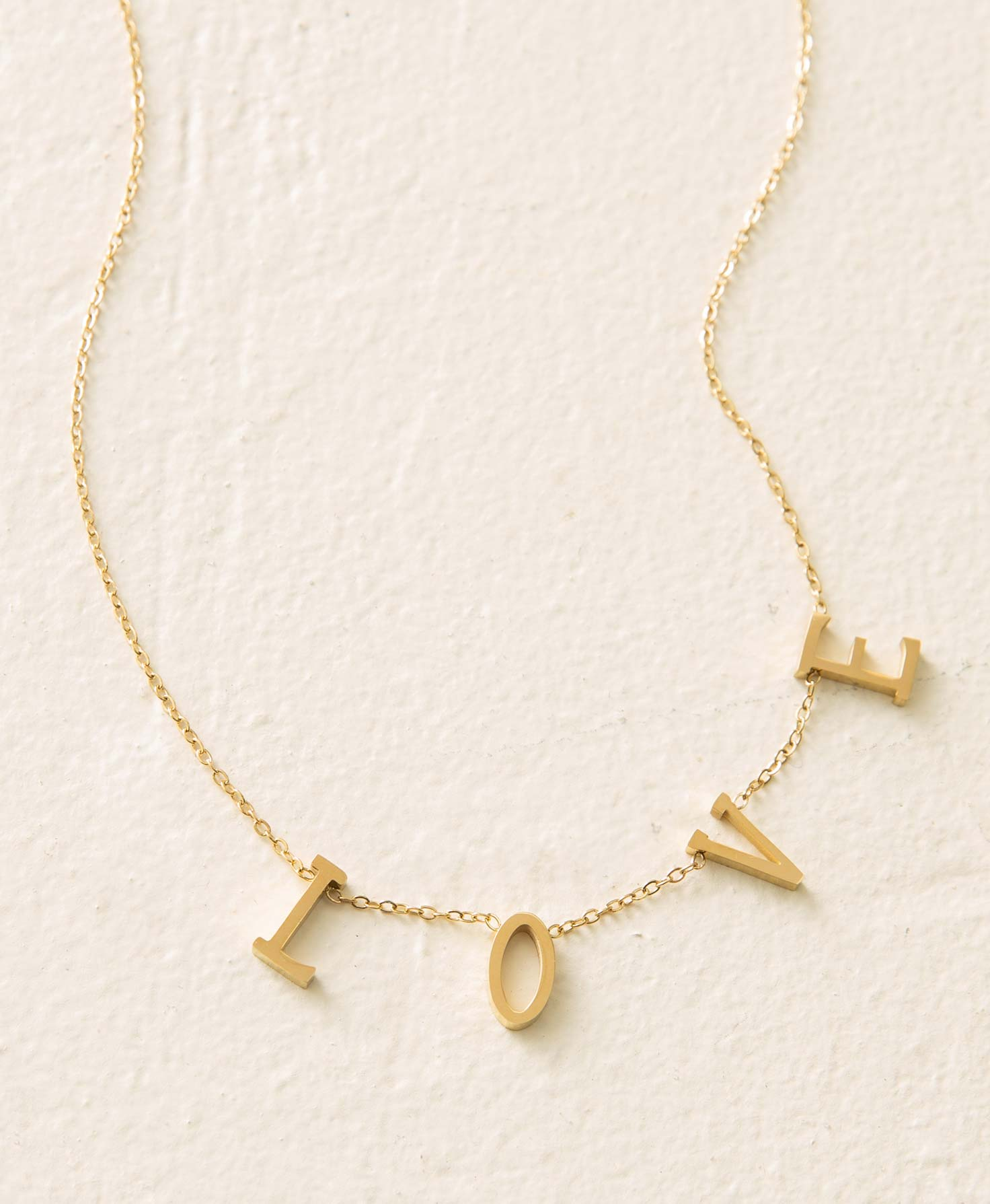 The Adored Necklace lays flat on a white surface. It features the letters L, O, V, and E, which are slightly three-dimensional and cut from gold plated stainless steel. The letters are affixed to a dainty gold chain. They are secured to the chain so they do not slide or move.