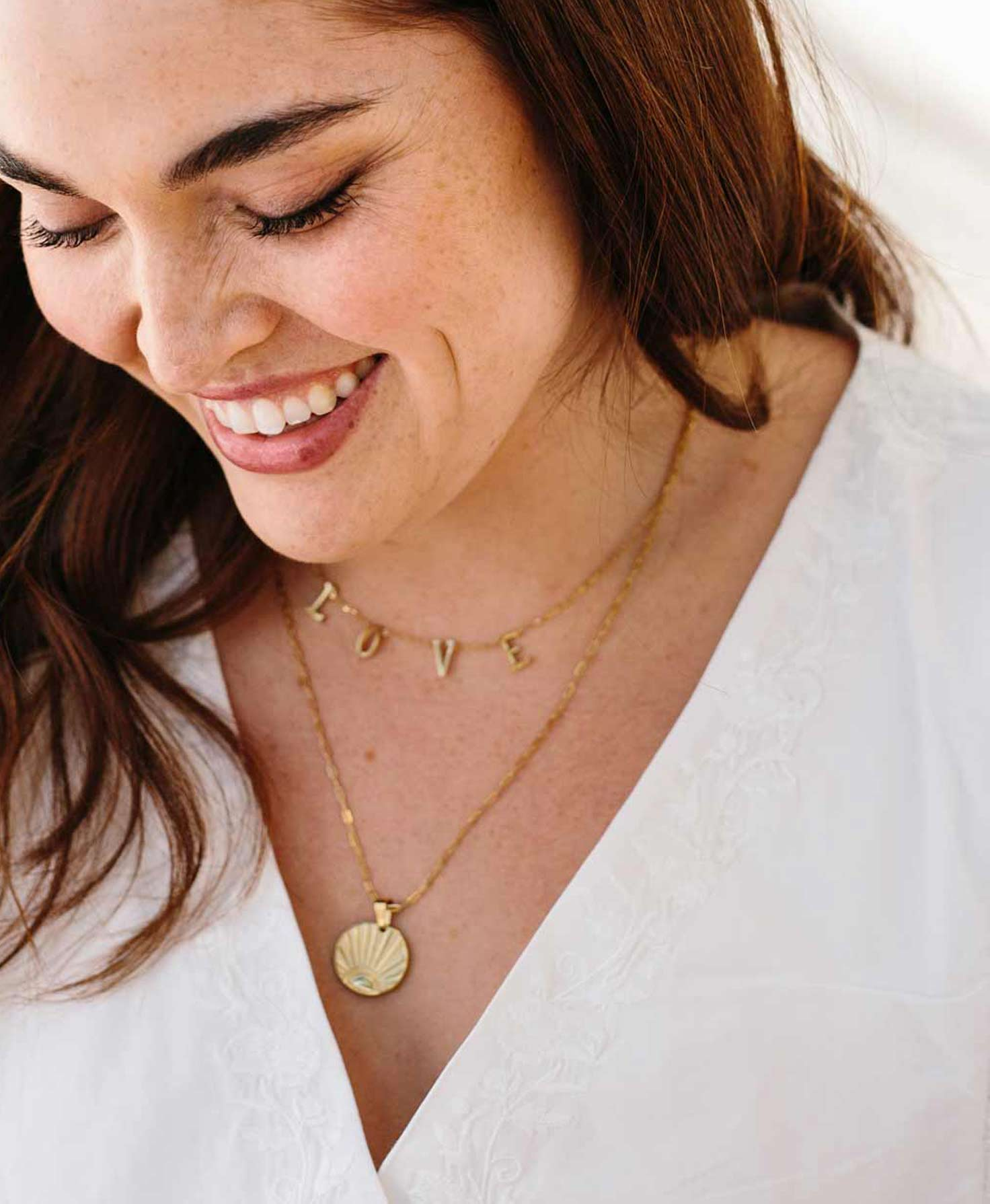 A model wears the short Beloved Necklace layered with the longer Sunrise Necklace for a long-and-short golden look.