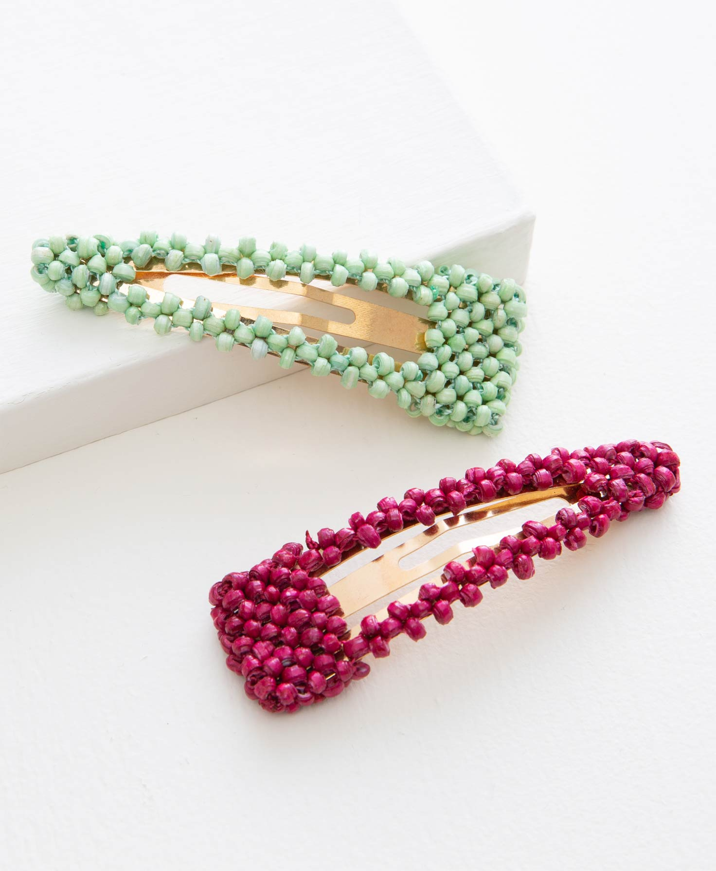 The two clips included in the Adorned Hair Clips Set lay flat on a white surface. This set features two large brass snap clips covered in tiny, hand-rolled paper beads. One clip is mint green, and the other is raspberry pink.