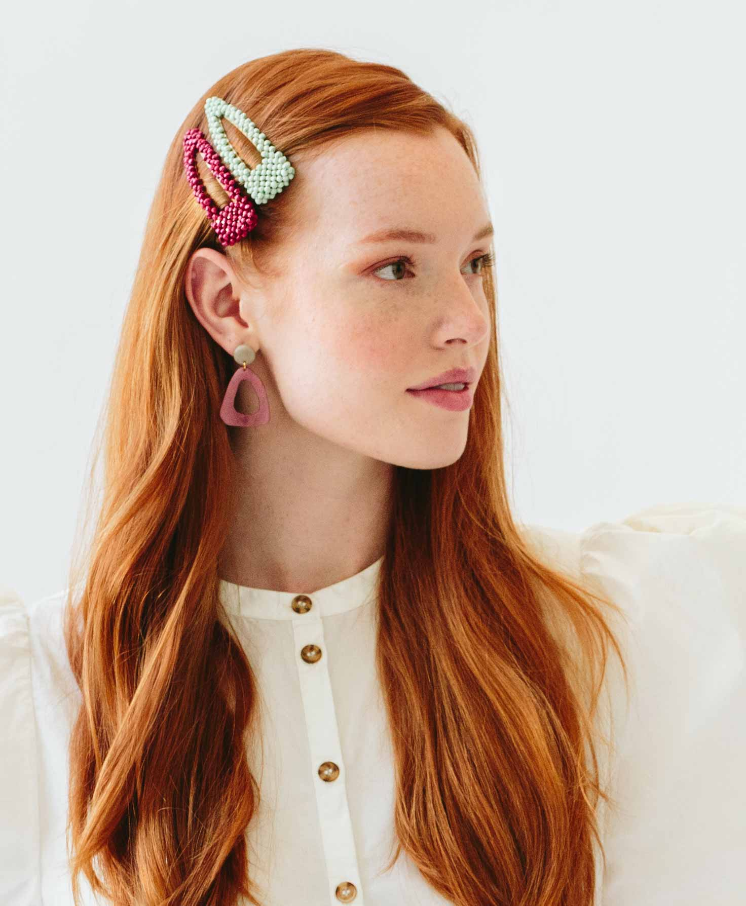 A model wears the Adorned Hair Clips on the side of her head. She wears both clips stacked vertically on top of one another for a colorful statement.