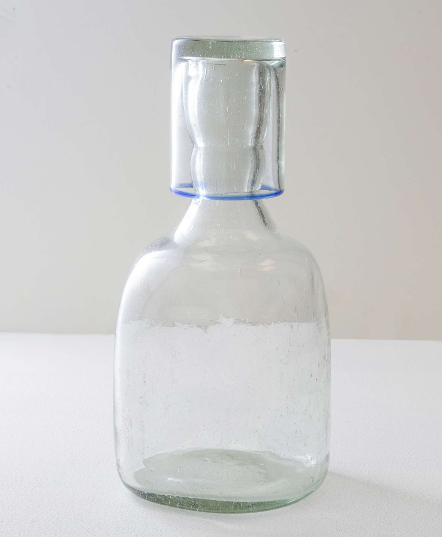 A large clear glass carafe sits upright. The glass has a handblown look with natural air bubbles throughout. The bottom section of the carafe is wide and round. It then tapers in and becomes narrower on top. A small glass rests upside down on the mouth of the carafe. It is the same clear glass as the carafe but with blue detailing along the mouth.