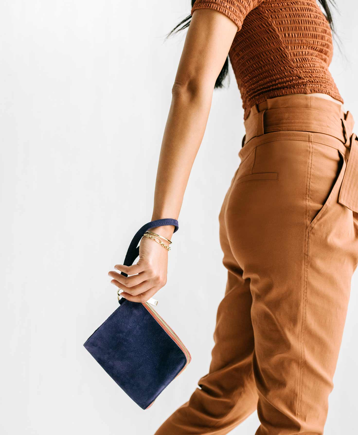 The image shows a model's back and arm, which swings behind her. She has the strap of the Amazement Pouch wrapped around her wrist, and the bag swings from her arm. The rich navy leather contrasts with the bag's shining brass zipper.