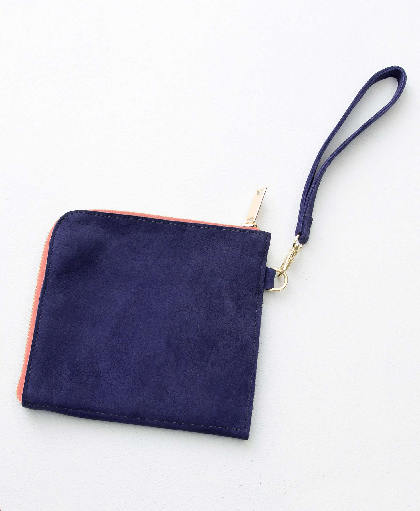 The Amazement Pouch lays on a white background. It is a square pouch with a golden zipper wrapping around one side and the top of the bag. It is made of soft navy leather. On the side of the bag is a small gold ring. A removable leather wrist strap in a matching navy shade is attached to the ring via a gold clip.