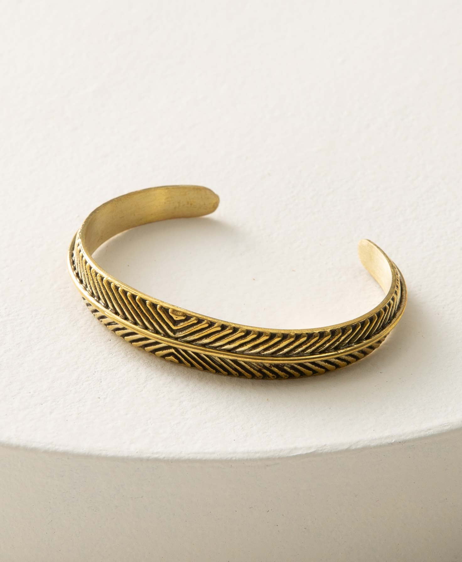 The Apex cuff sits on a white circular block. It is a brass cuff with an opening in the back that allows the wearer to slide it on and off. The brass features a repeating geometric pattern made up of angled lines running around the entire cuff, creating a chevron-like effect. A thin strip of brass runs through the center of the pattern.