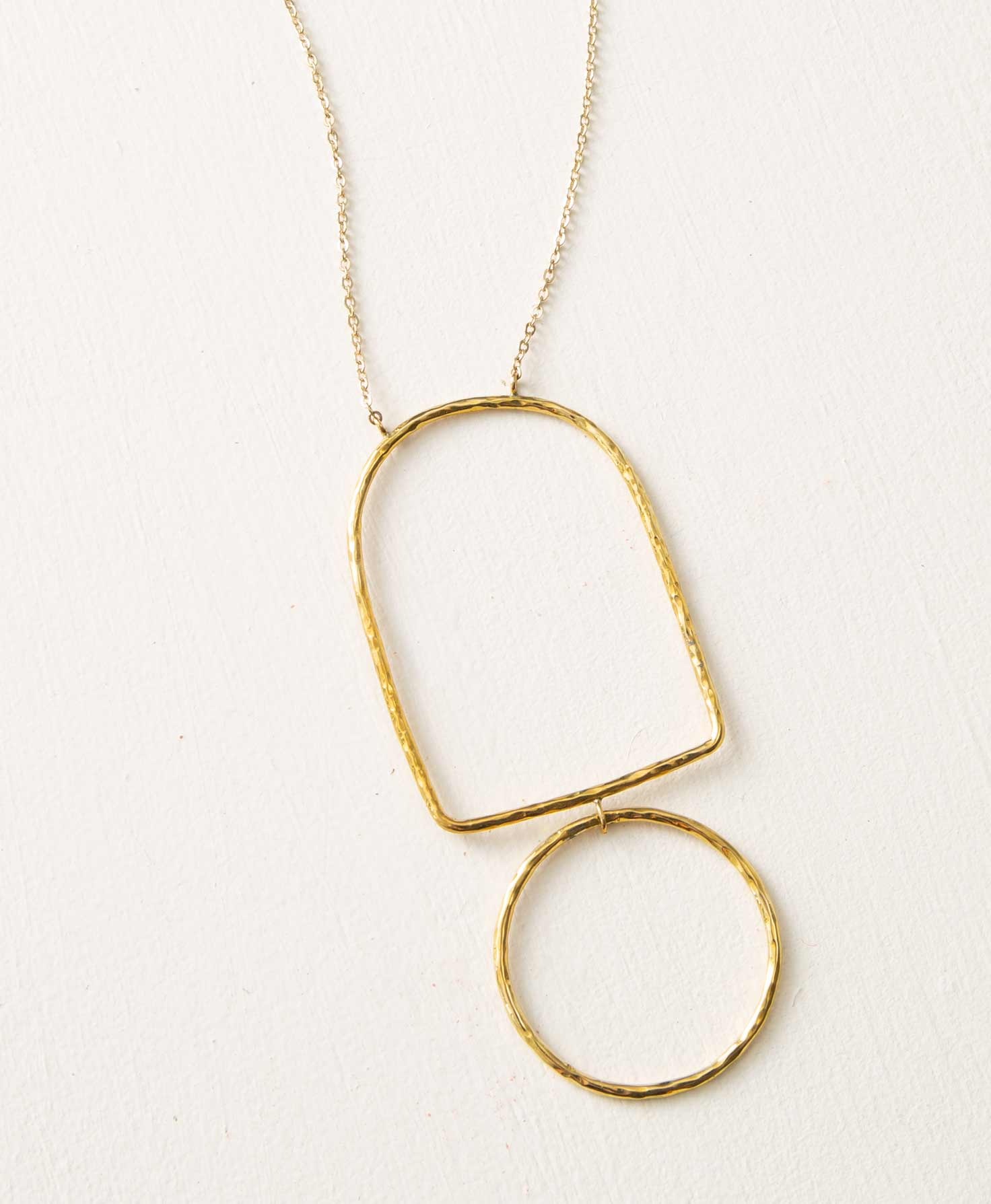 The Arcade Necklace rests on a flat white surface. A long brass-colored chain is accented with a large brass pendant. The pendant is made of rods of hammered brass formed into geometric shapes. There is a rounded rectangle-shaped piece linked to a circle-shaped piece below it. The pendant is affixed so it does not slide on the chain.