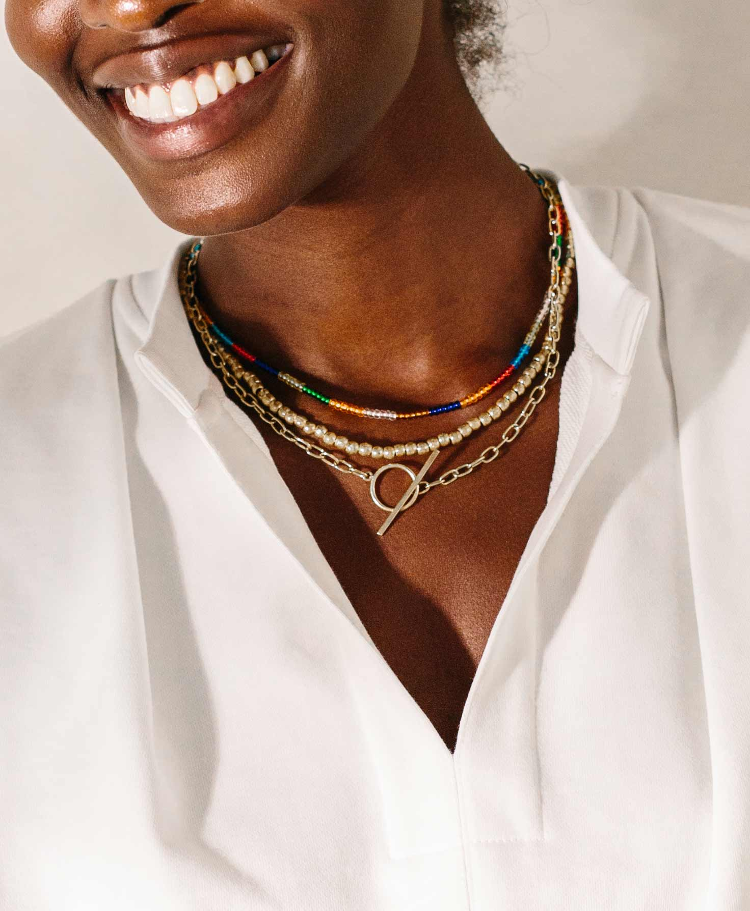 A model wears the short Artillery Pearl Necklace with two other short necklaces, the Infinity Necklace and Chromatic Necklace. Together, the necklaces create a layered choker look.