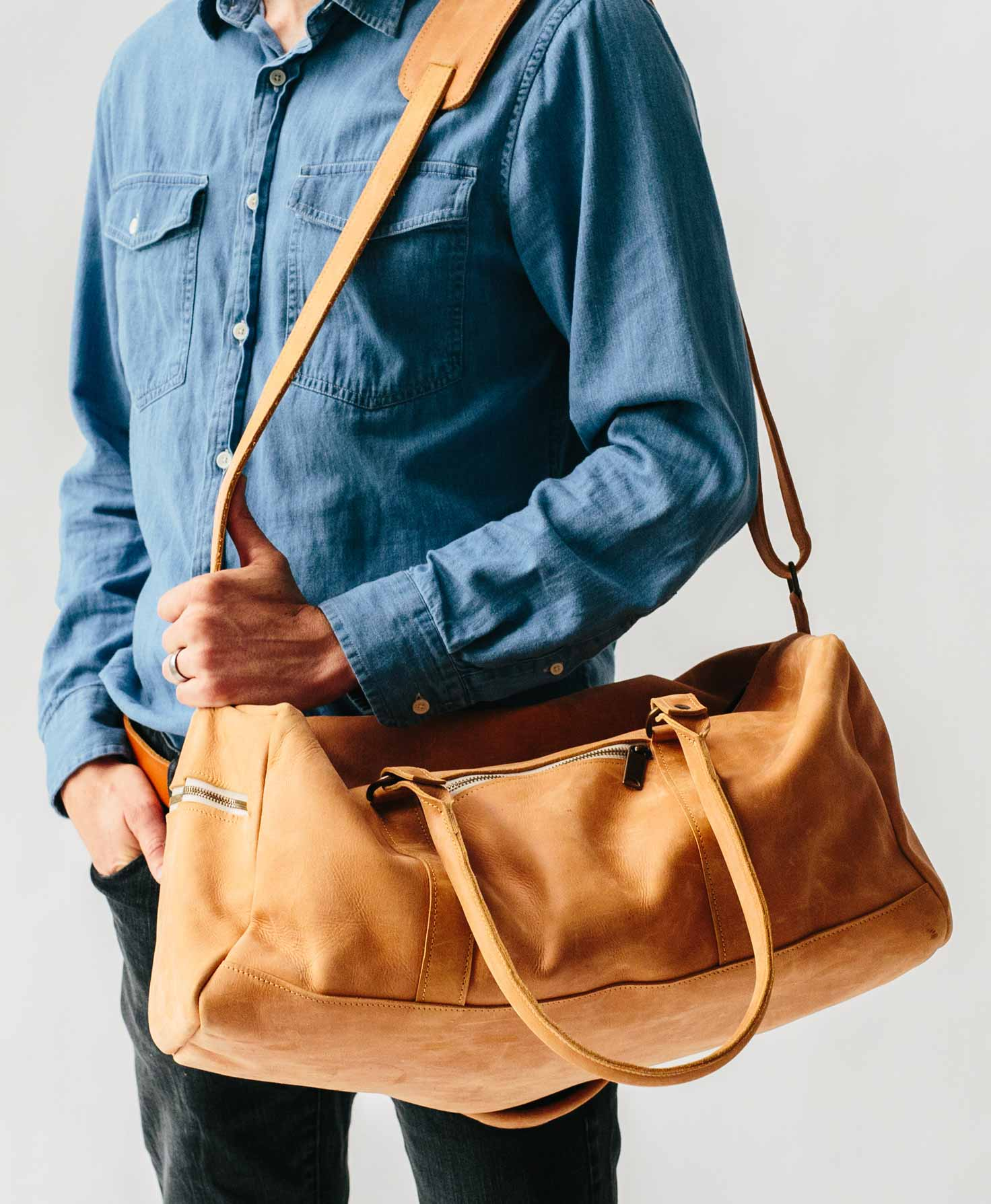 A male model is shown holding the Awasa Weekender Bag. He wears the bag on his shoulder, and it hangs down slightly below his waist.