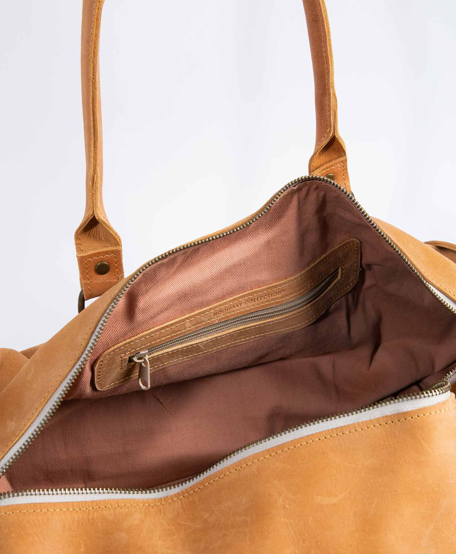 The Awasa Weekender Bag is unzipped, revealing its interior. The lining of the bag is a solid light-brown color. Inside the bag is a small zipper compartment. The zipper is outlined in leather, and
