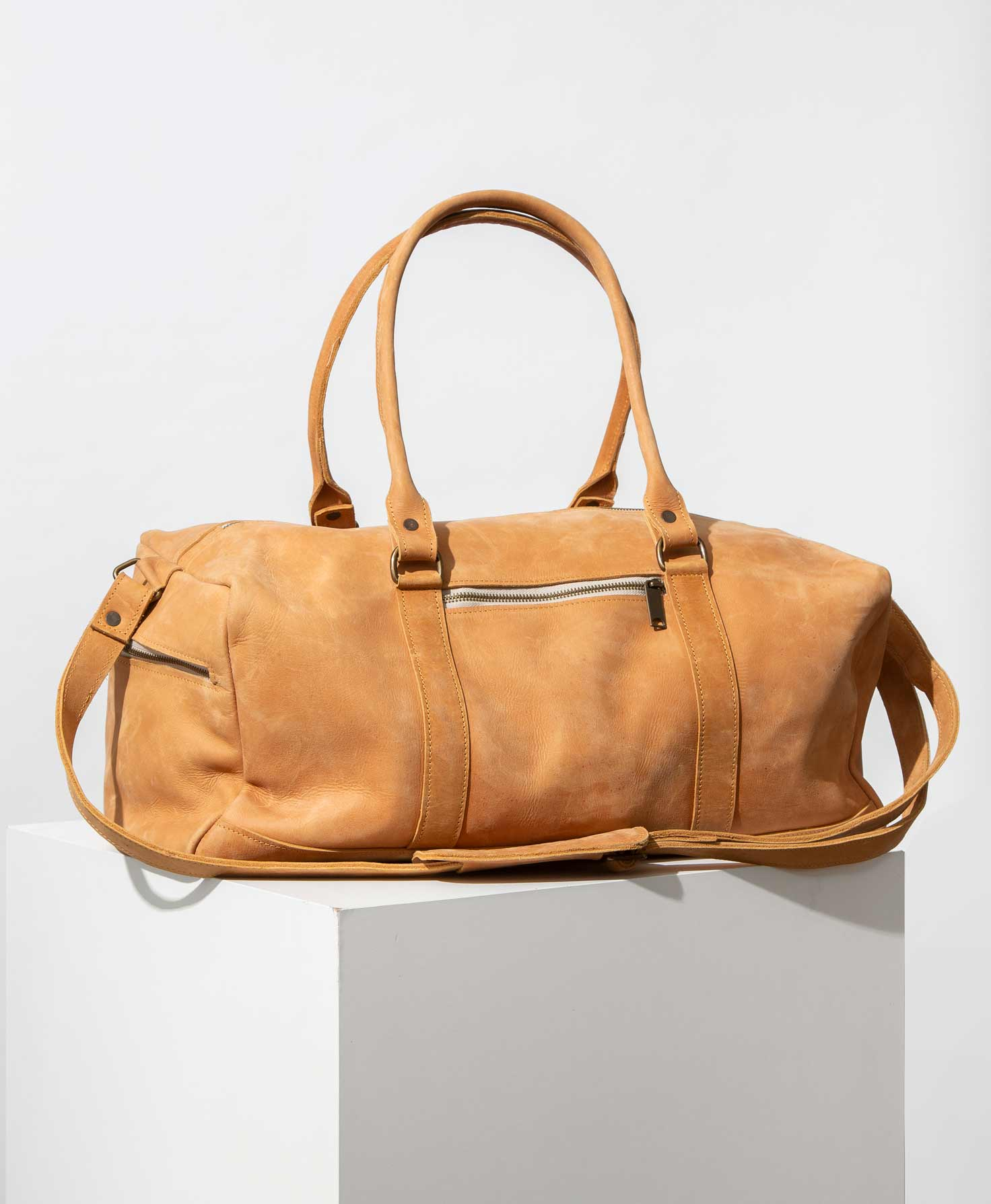 The Awasa Weekender Bag sits on top of a white platform. It is a duffel-style bag made of smooth leather in a shade of light caramel. All of the hardware is bronze-colored. On one end of the bag, there is a zipper pocket. There is another zipper pocket on one of the sides. There are two short, structured leather handles, as well as one long leather strap that can be adjusted or removed.