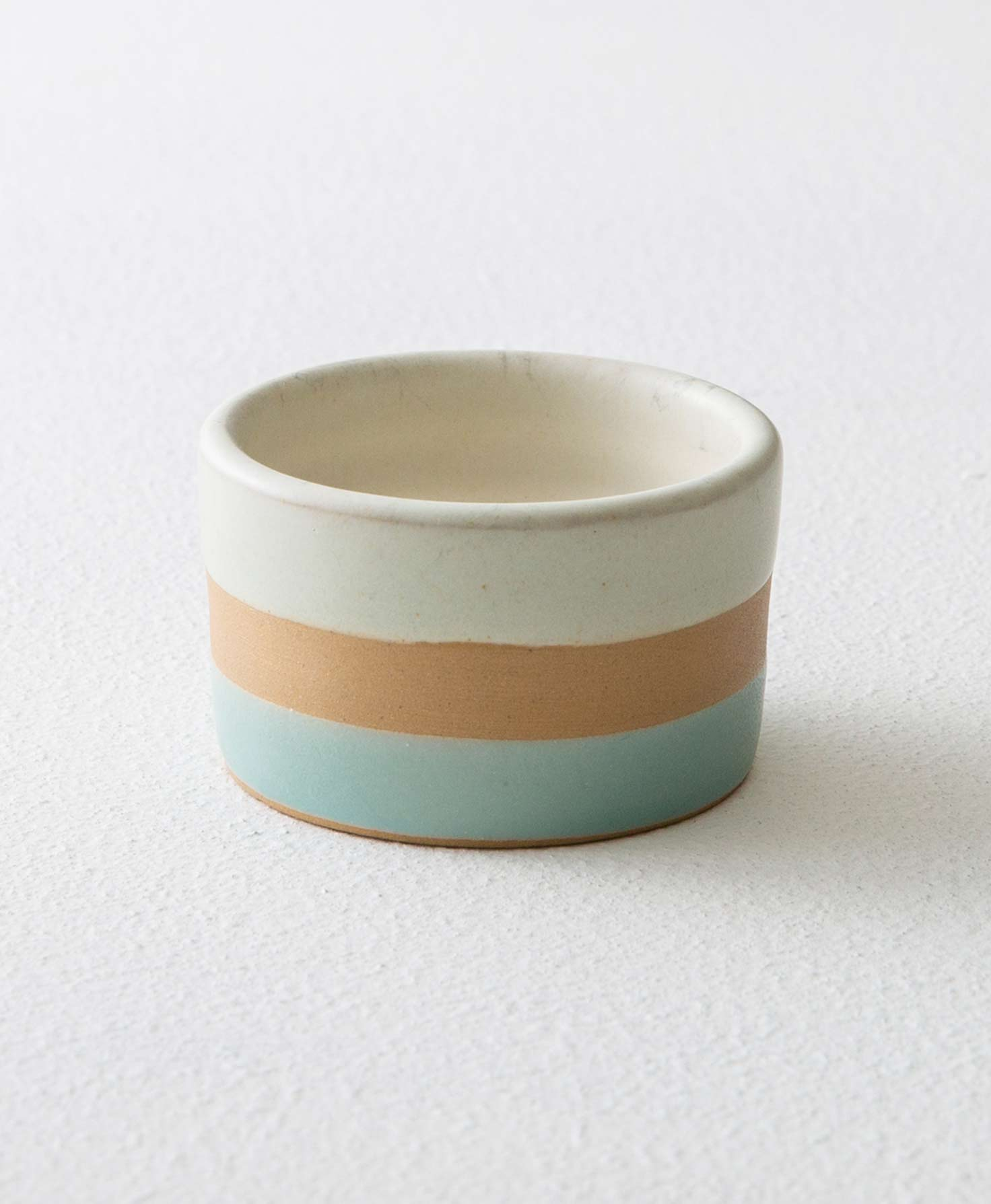 The Banded Stone Tealight Holder in Green sits on a white surface. It is made of smooth stoneware that forms a short, rounded vessel. The stoneware is divided into three different horizontal stripes of color that wrap around the vessel. The bottom stripe is mint green, the middle stripe is tan, and the top stripe is light mint.