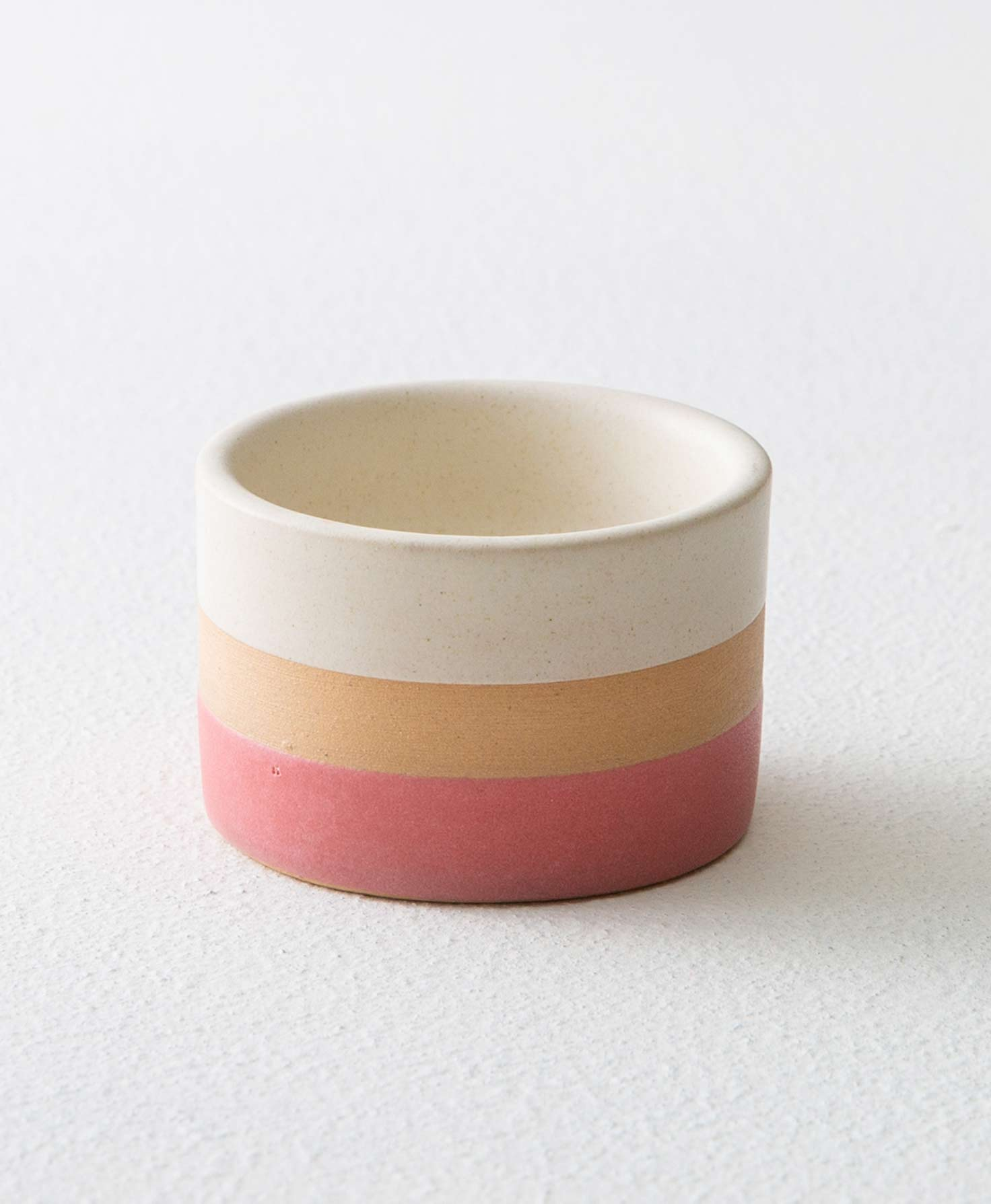 The Banded Stone Tealight Holder in Pink sits on a white surface. It is made of smooth stoneware that forms a short, rounded vessel. The stoneware is divided into three different horizontal stripes of color that wrap around the vessel. The bottom stripe is a rosy pink, the middle stripe is tan, and the top stripe is cream.
