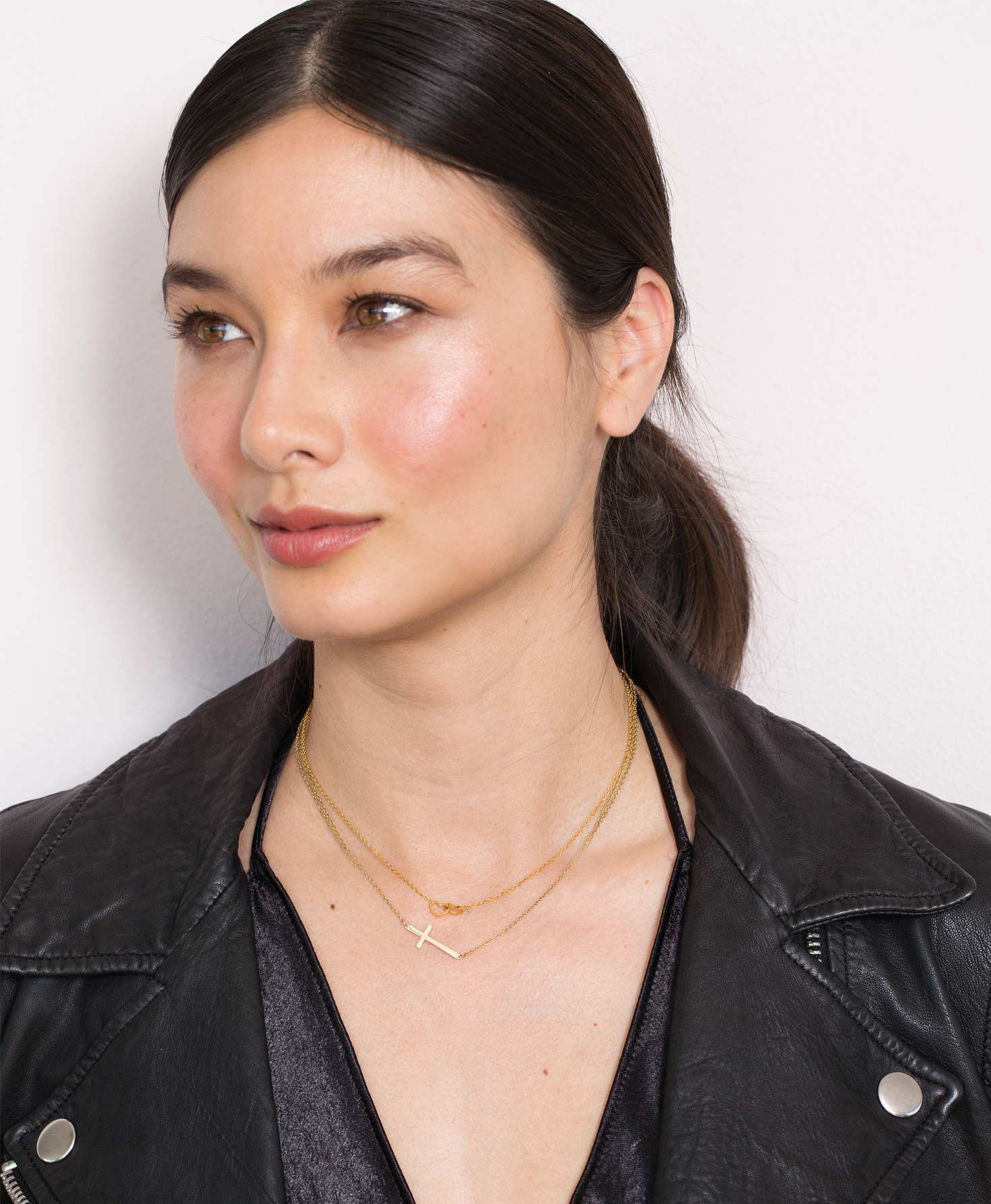 A model wears the short gold Belief Necklace with the Heart to Heart Necklace, which is another short gold necklace. The two together create a dainty golden look.