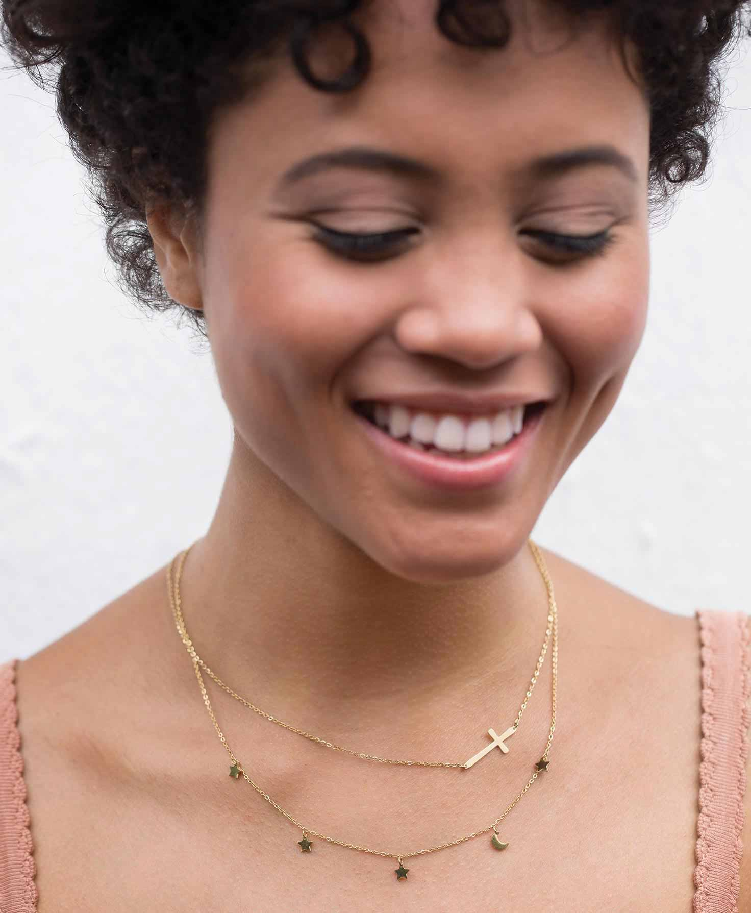 A model wears the Belief Necklace in Gold with the golden Destiny Necklace, which hangs down slightly lower for a layered look.