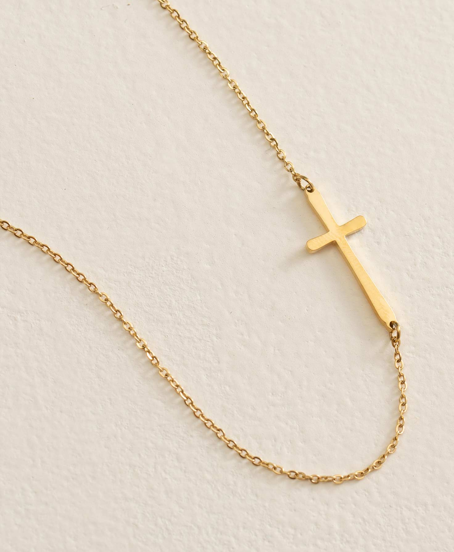 The Belief Necklace in Gold lays flat on a cream-colored surface. It features a gold plated stainless steel chain. A dainty gold cross is joined to the chain via jump rings at the top and bottom of the cross. The cross can be positioned horizontally at the bottom of the necklace or positioned vertically by rotating the necklace. This short necklace can be adjusted via the extender chain at the back.