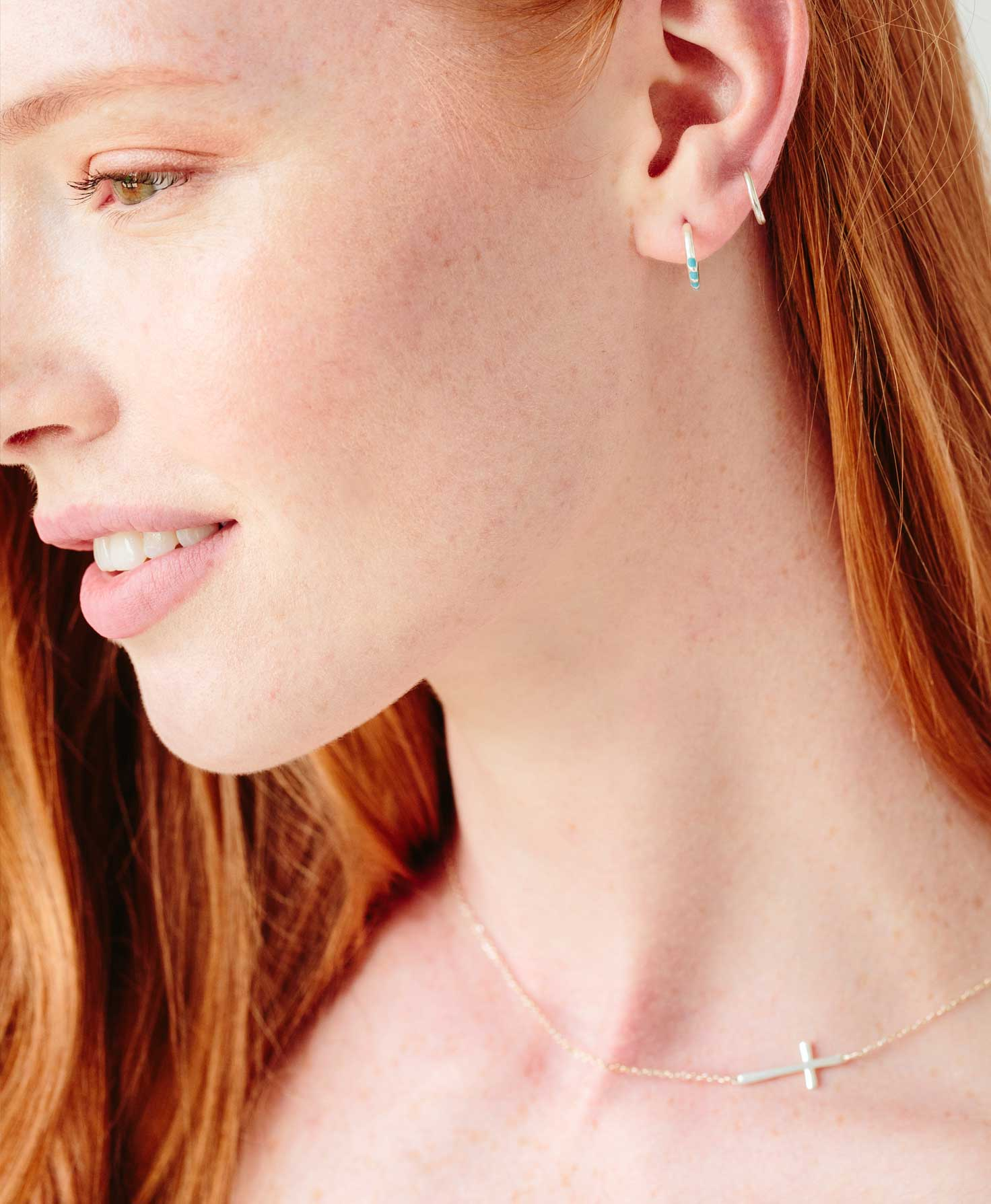 For a simple everyday feel, a model wears the Belief Necklace in Silver by itself. She accents the look with a pair of silver dainty hoops.