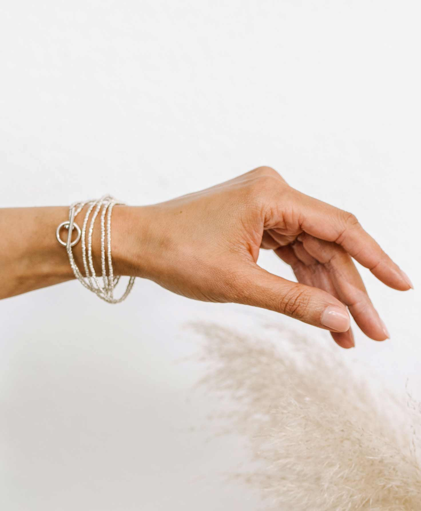 A woman's arm is shown wearing the Bichena Bracelet. The bracelet wraps around her wrist six times for a layered look. The silver metal beads catch the light and shine.