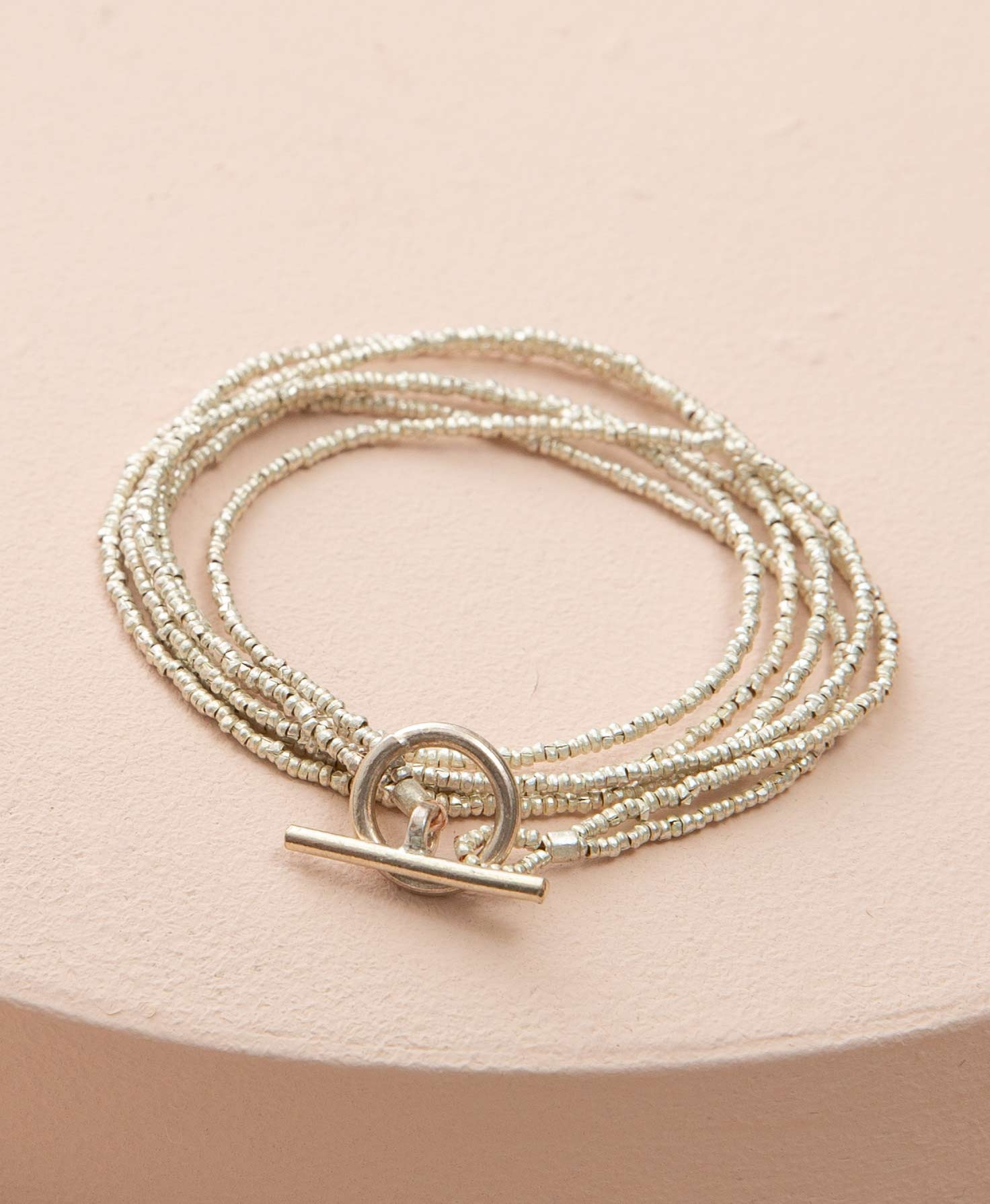 The Bichena Bracelet lays coiled on a peach-colored block. It is a wrap style bracelet composed of strands of tiny silver metal beads. The strands wrap around multiple times for a dainty layered look. They end in a lariat-style closure, with a silver bar that slides through a silver loop to secure the bracelet.