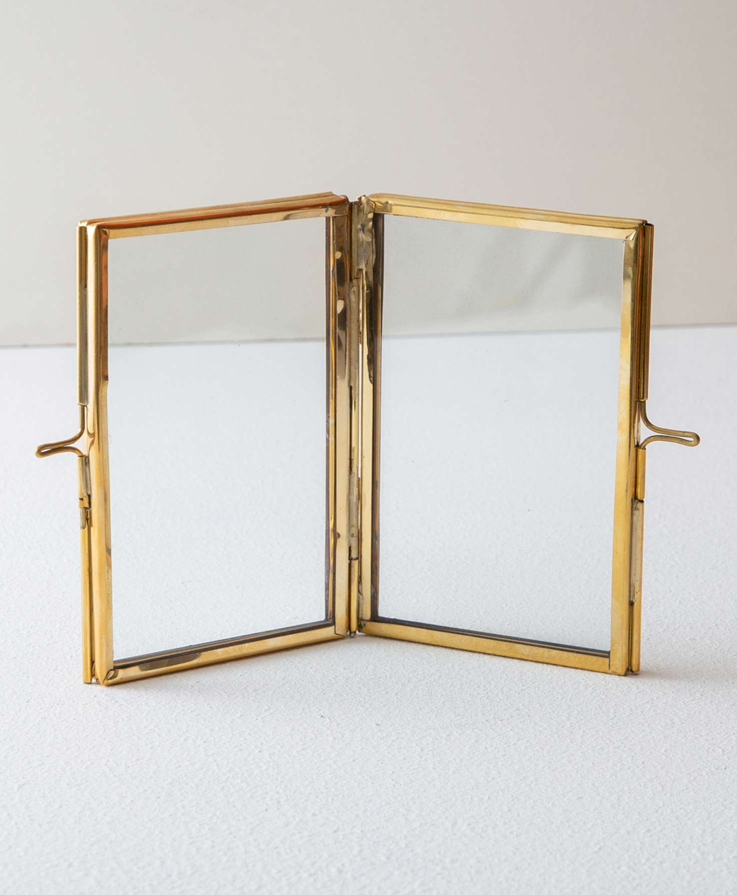 The Brass and Glass Double Frame stands upright and is slightly propped open. Two rectangular glass panels are framed with shining brass. The two panels are connected via a brass hinge in the center. On the two outer edges of the frames, a mechanism enables the brass frame to open so that a photo may be placed between the glass and the frame.