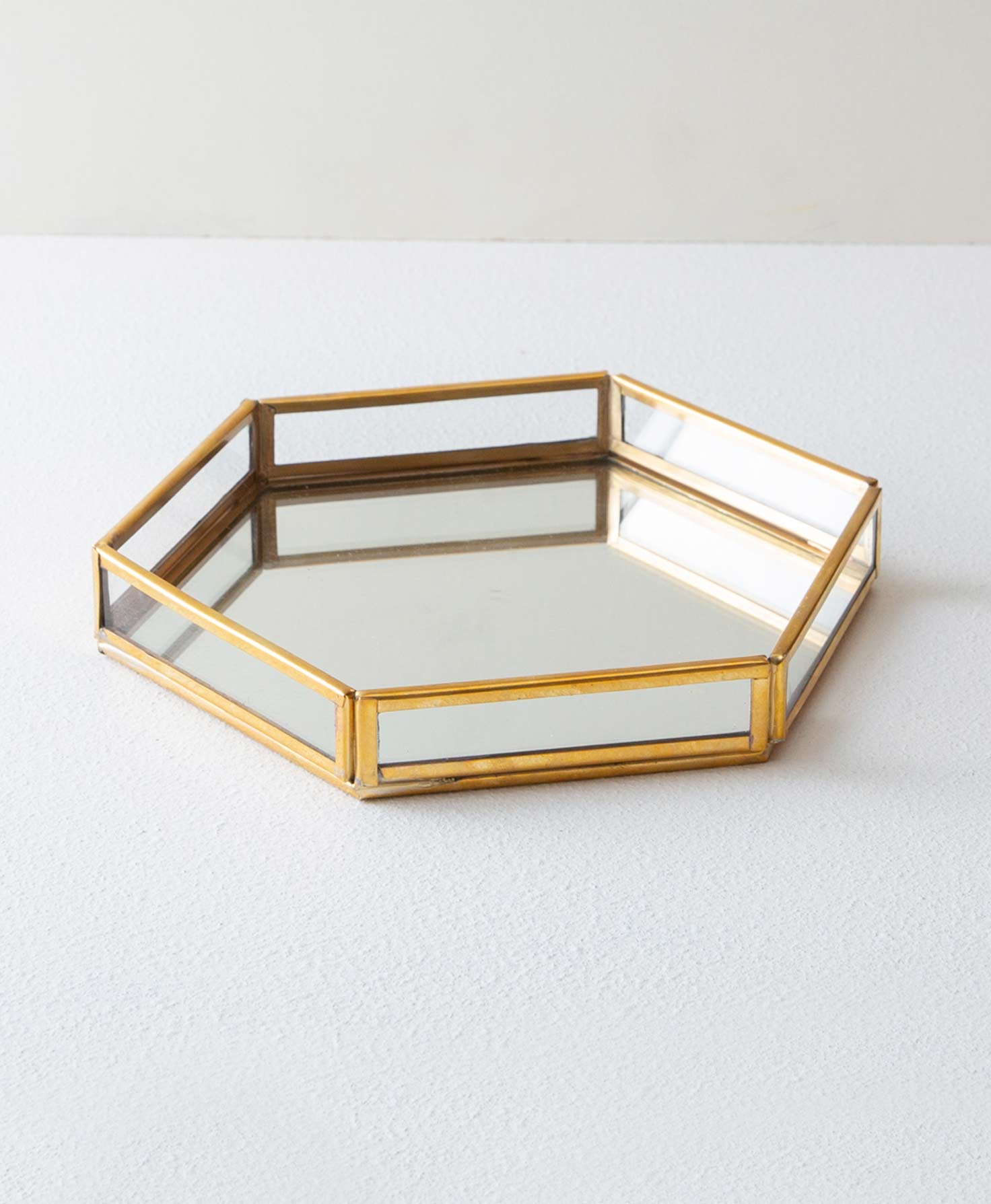 The Brass and Glass Hexagonal Tray sits on a white surface. It has six low sides composed of a rectangular glass panels framed in shining brass. The base of the tray is a hexagon made of mirrored glass.
