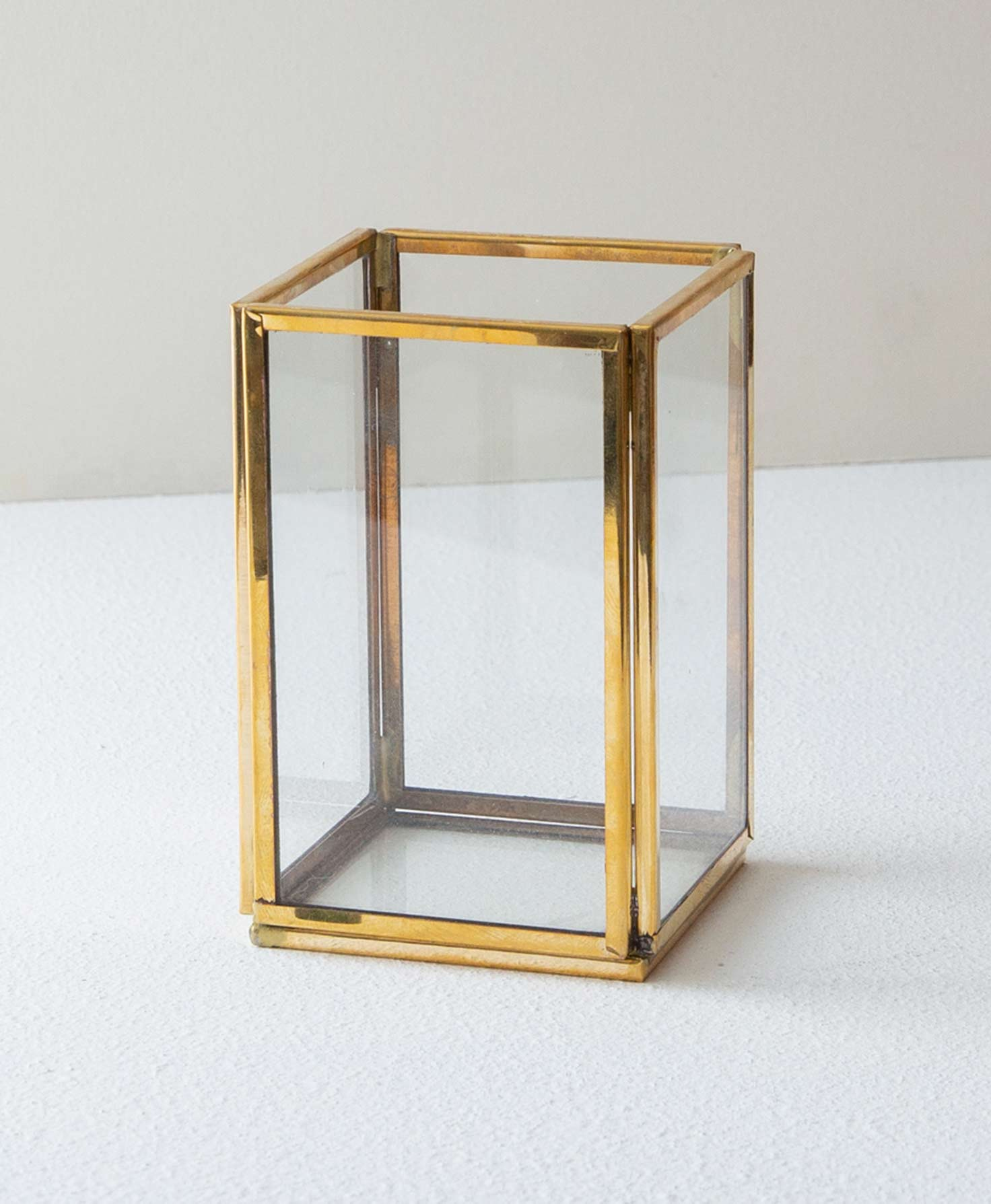 The Brass and Glass Penholder sits on a white surface. It has a square glass base framed in shining brass. Four vertical, rectangular glass panels outlined in brass form the sides of the penholder. It is open on top.
