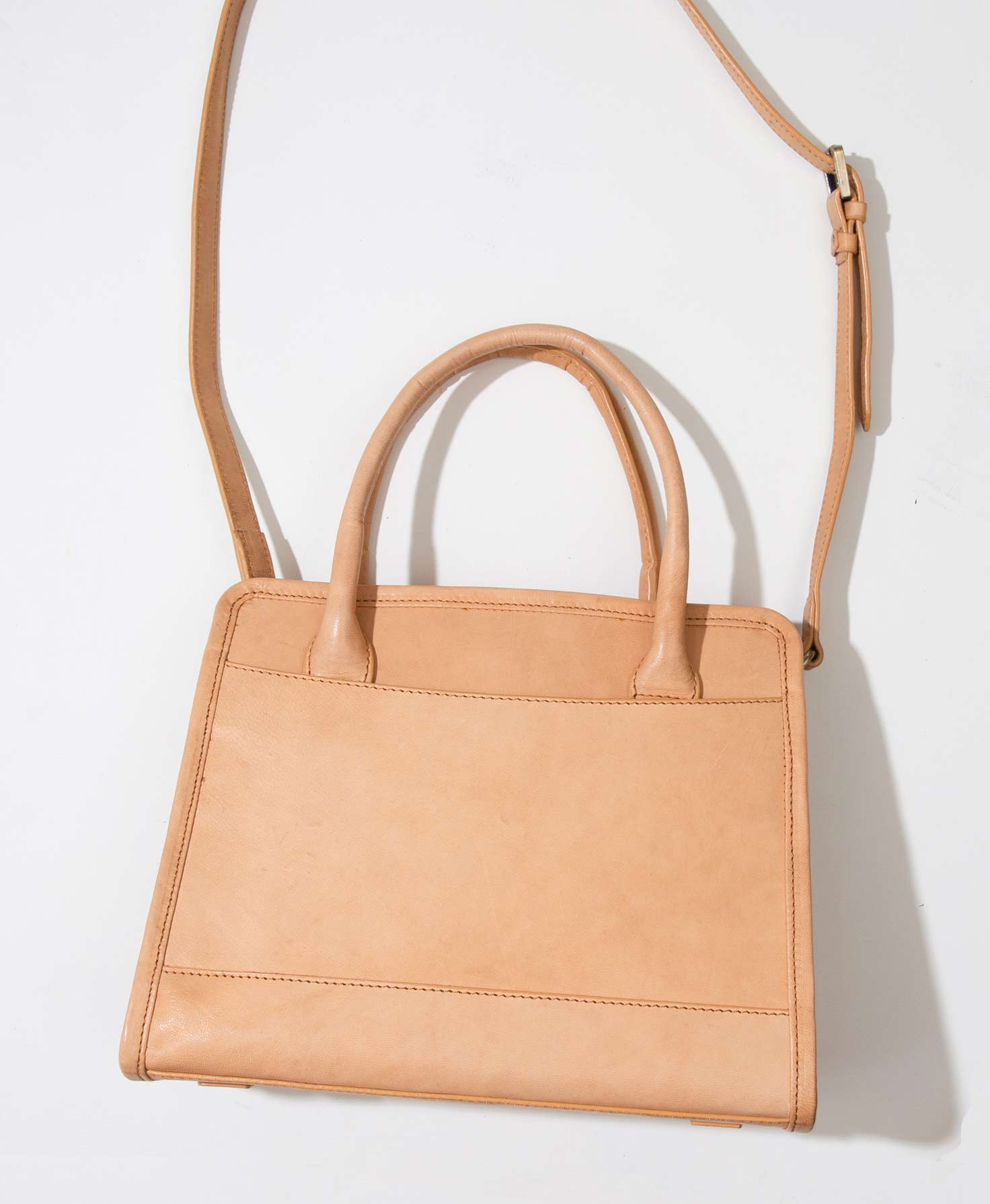 The Bravo Bag sits upright on a white platform. It is made of light caramel-colored leather and has a roughly square shape. It is slightly wider than it is high. The bag has a flat bottom panel, allowing it to sit upright. It has a minimal design with no markings or embellishments. The bag closes via a small leather flap that folds over and is secured via a magnetic closure. There are two leather handles at the top of the bag, as well as a removable leather strap that can be adjusted via a brass buckle.