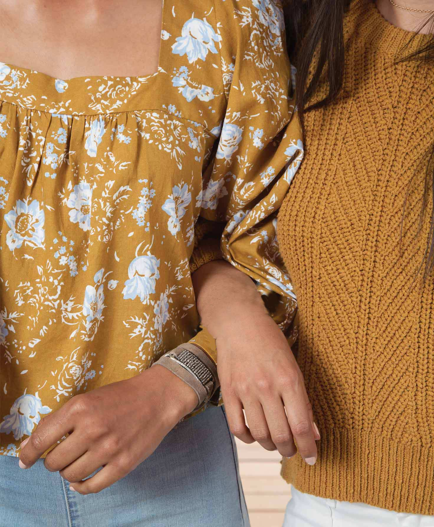 Two models are shown with their arms linked together. One model wears the Brilliant Leather Wrap Bracelet wrapped around her wrist for a subtle, sparkling accent.