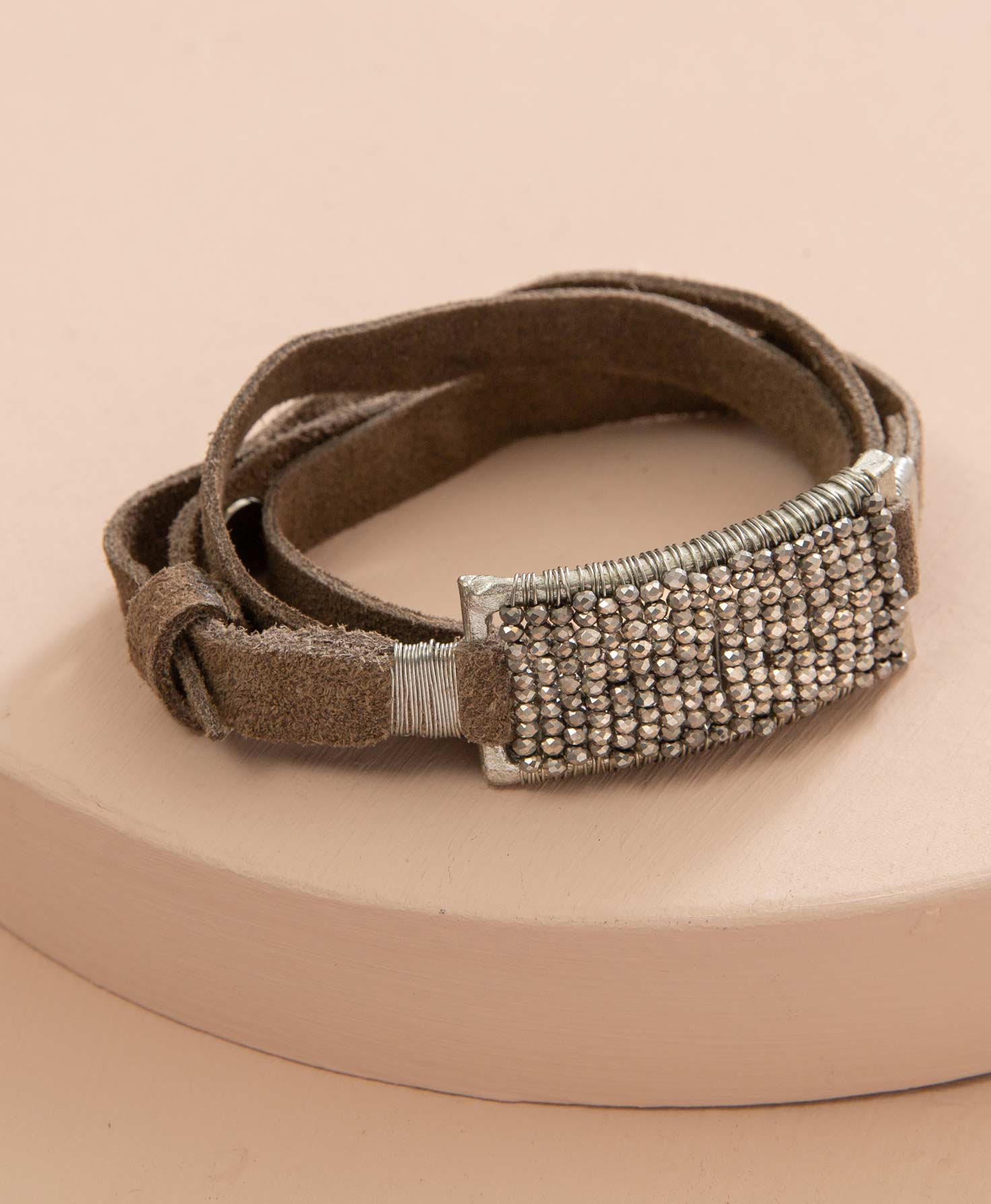 The Brilliant Leather Wrap Bracelet lays coiled on a round platform. The bracelet is composed primarily of a soft, smoky brown suede strip that wraps around the wrist. In the center of the bracelet is a rectangular, hammered silver piece. Dozens of faceted silver glass beads are strung in rows across the rectangle.