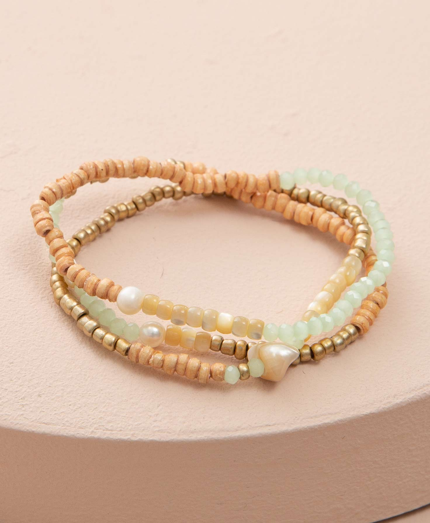 The three bracelets included in the By the Sea Bracelet set lay stacked on a cream-colored platform. The bracelets are made of stretchy elastic with small beads strung along them. While the bracelets vary slightly, they are relatively similar in appearance. The bracelets feature tan paper beads, cream-colored glass beads, mint-colored glass beads, brass-colored glass beads, and pearls.