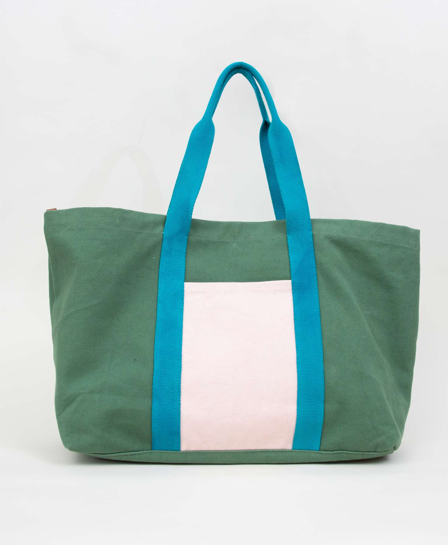 The Canvas Colorblock Carryall sits upright on a white surface. It is a large tote that is rectangular in shape. It is wider than it is high. The bag is made of three different colors of canvas. The main color is forest green. Onto this is stitched a large cream canvas pocket. Stretching from the bottom of the bag all the way to the top are two turquoise canvas strips that become the bag's two handles.