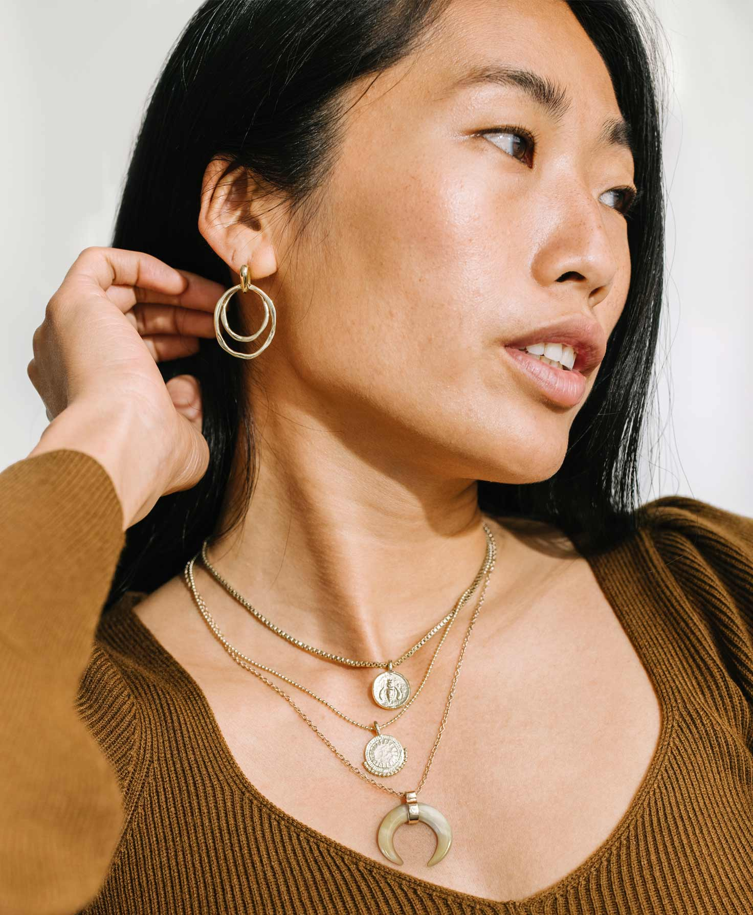 A model wears the two Charmed Medallion Necklaces layered with the Fable Necklace, another gold necklace with a neutral color palette. She finishes her metallic look with the golden Wild Link Earrings.