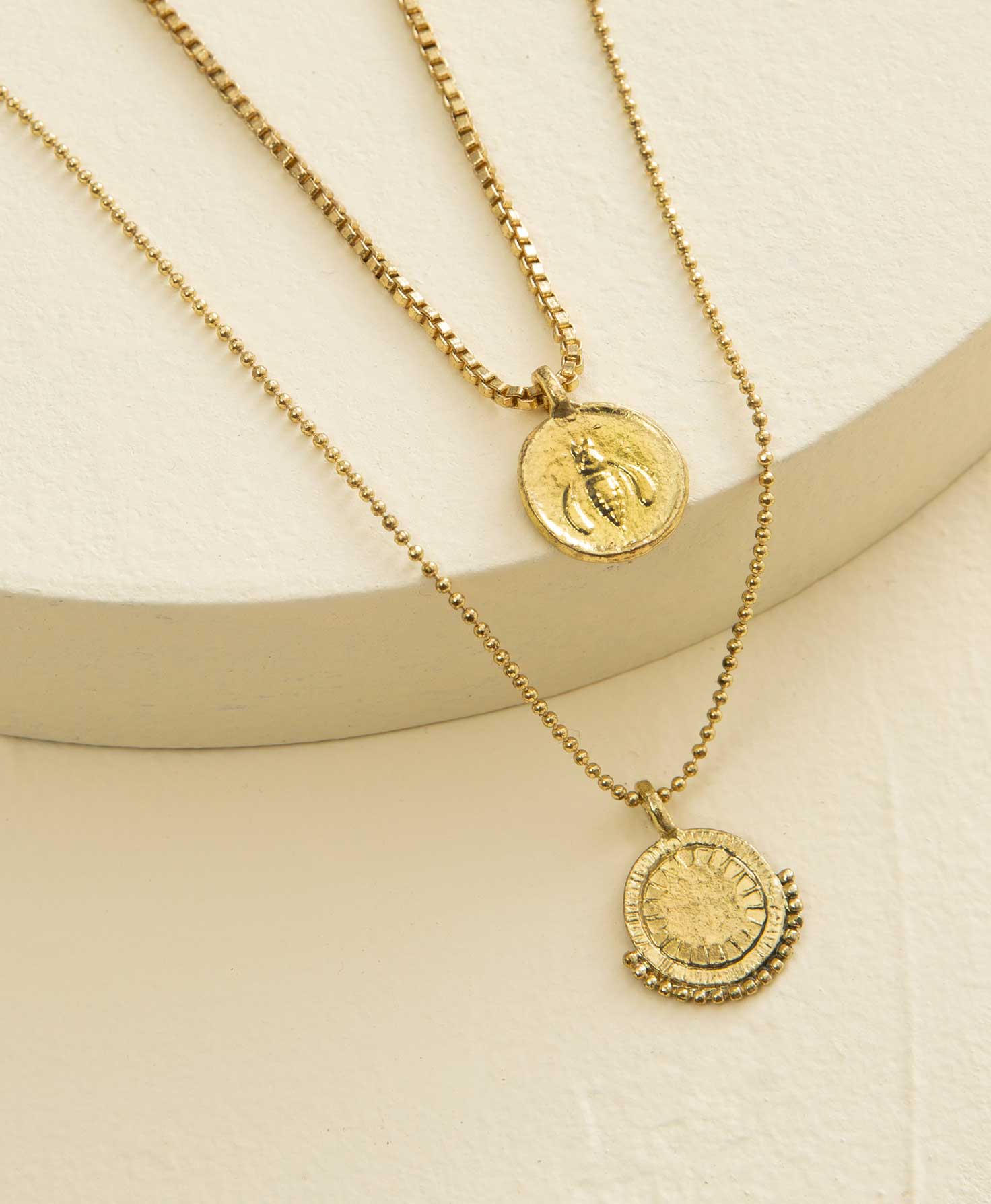 The two gold necklaces included in the Charmed Medallion Necklace set lay draped over a cream-colored platform. The varying necklace lengths allow the two necklaces to be worn layered together or by themselves. The longer necklace has a ball-style chain and a circular gold pendant with a row of small golden balls lining the bottom half of the circle. The shorter necklace has a rectangular-style chain and a circular gold pendant embellished with an image of a bee.