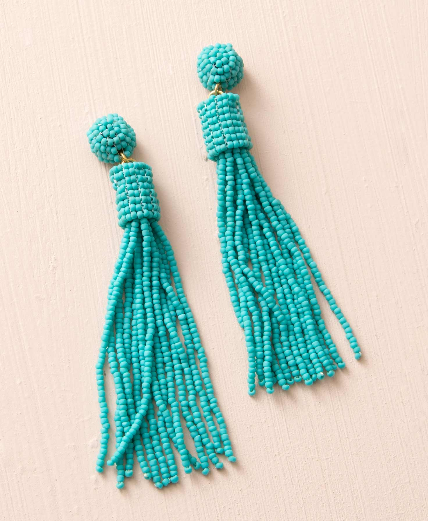 The Chime earrings lay against a cream background. They are chandelier-style earrings composed of teal glass beads. The posts are embellished with a ball made of these glass beads. Below, brass jump rings connect the post to a short tube of glass beads. Beneath this, around 15 long strands of glass beads swing down.