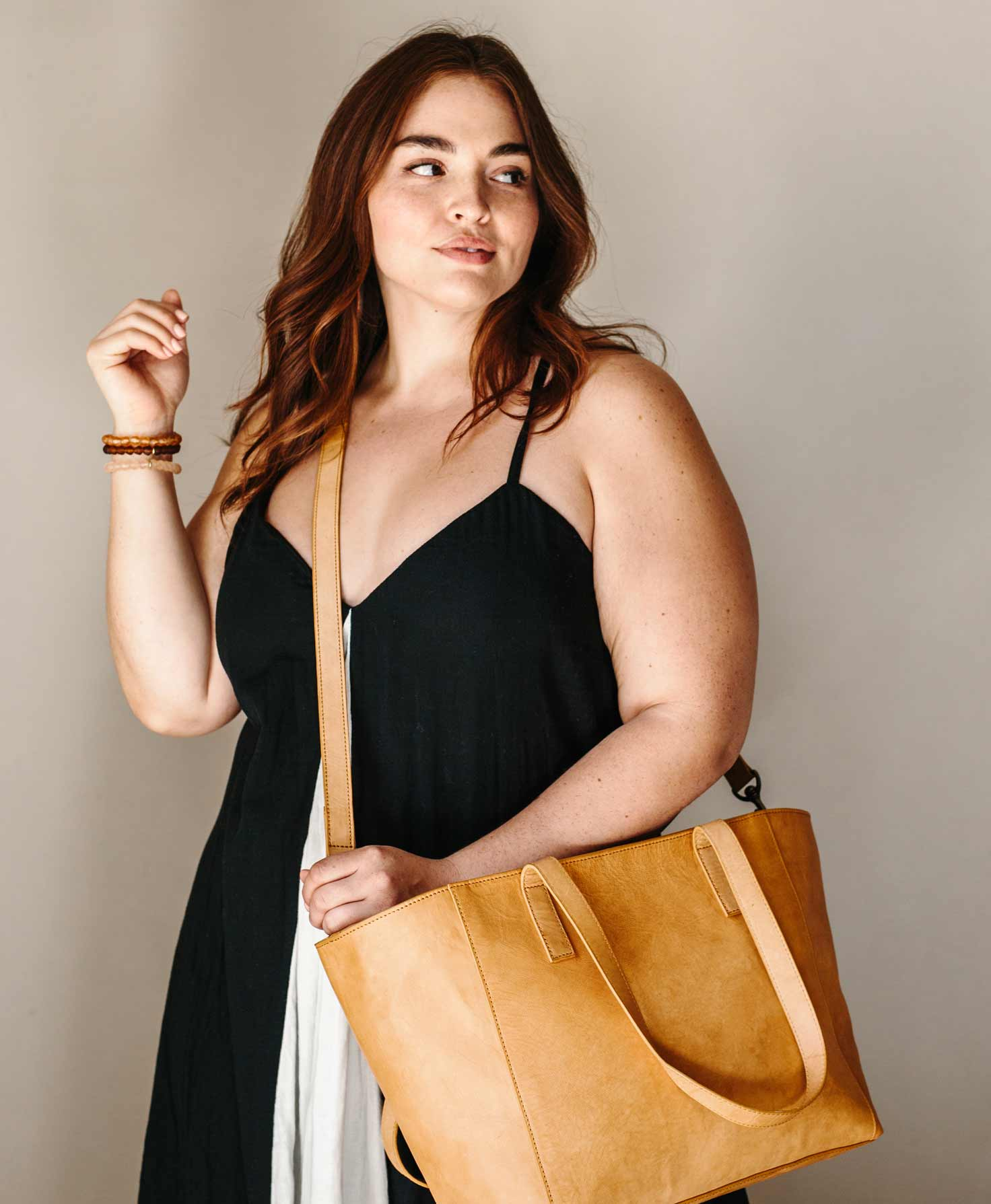 A model wears the City Tote with its long strap attached for a crossbody style. It hangs down just below her hip.