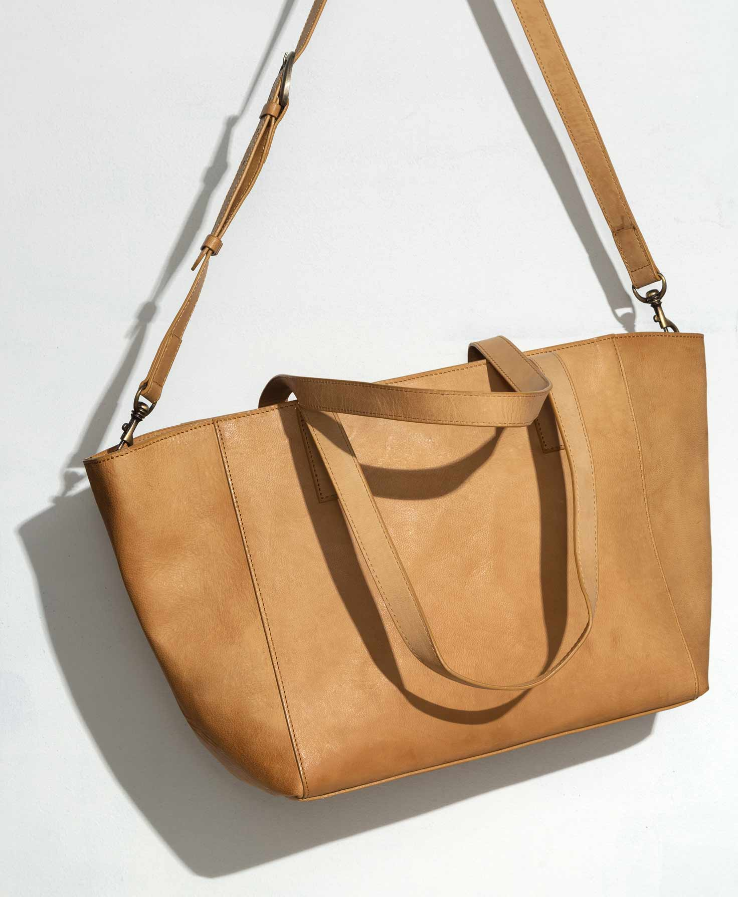 The City Tote is shown hanging against a white wall. It is a wide, roughly rectangular tote that is wider than it is tall. It is made of smooth, light caramel colored leather. There are two short leather handles in the center of the bag. On the edges of the bag, bronze hardware clips connect a long leather strap that can be adjusted or removed. The bag has a zip closure along the top.