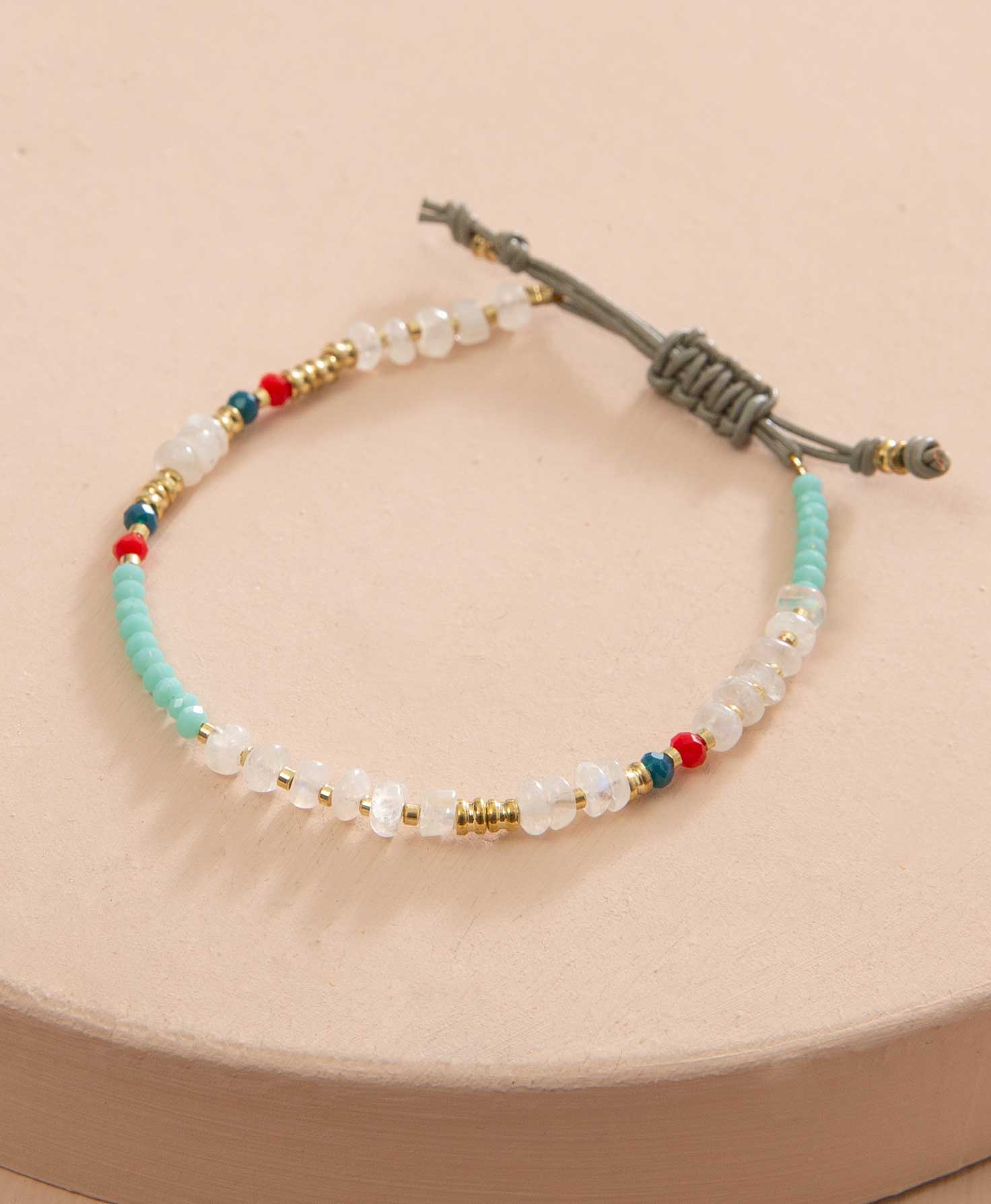 The Clarity Bracelet lays flat against a cream background. It features beads strung along a glossy grey leather cord that can be adjusted by pulling both ends. The cord is lined with an assortment of faceted moonstone beads, small brass beads, and faceted glass beads in shades of aqua, navy, and red.