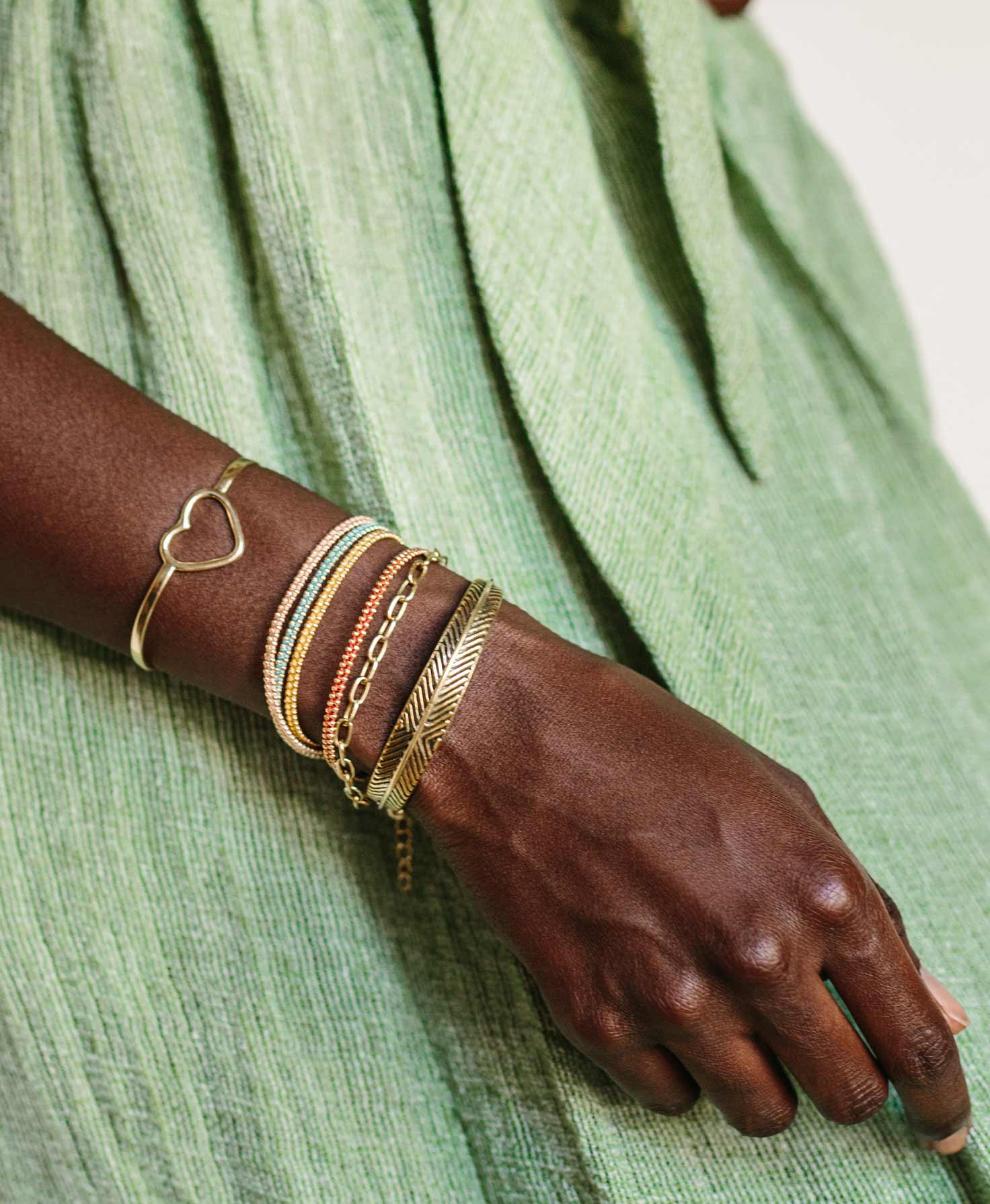 A model's arm is shown resting against her side. On her wrist she wears the Color Blocked Wrap Bracelet paired with a stack of other bracelets, including the Apex Cuff, Expression Cuff, and Infinity Bracelet.