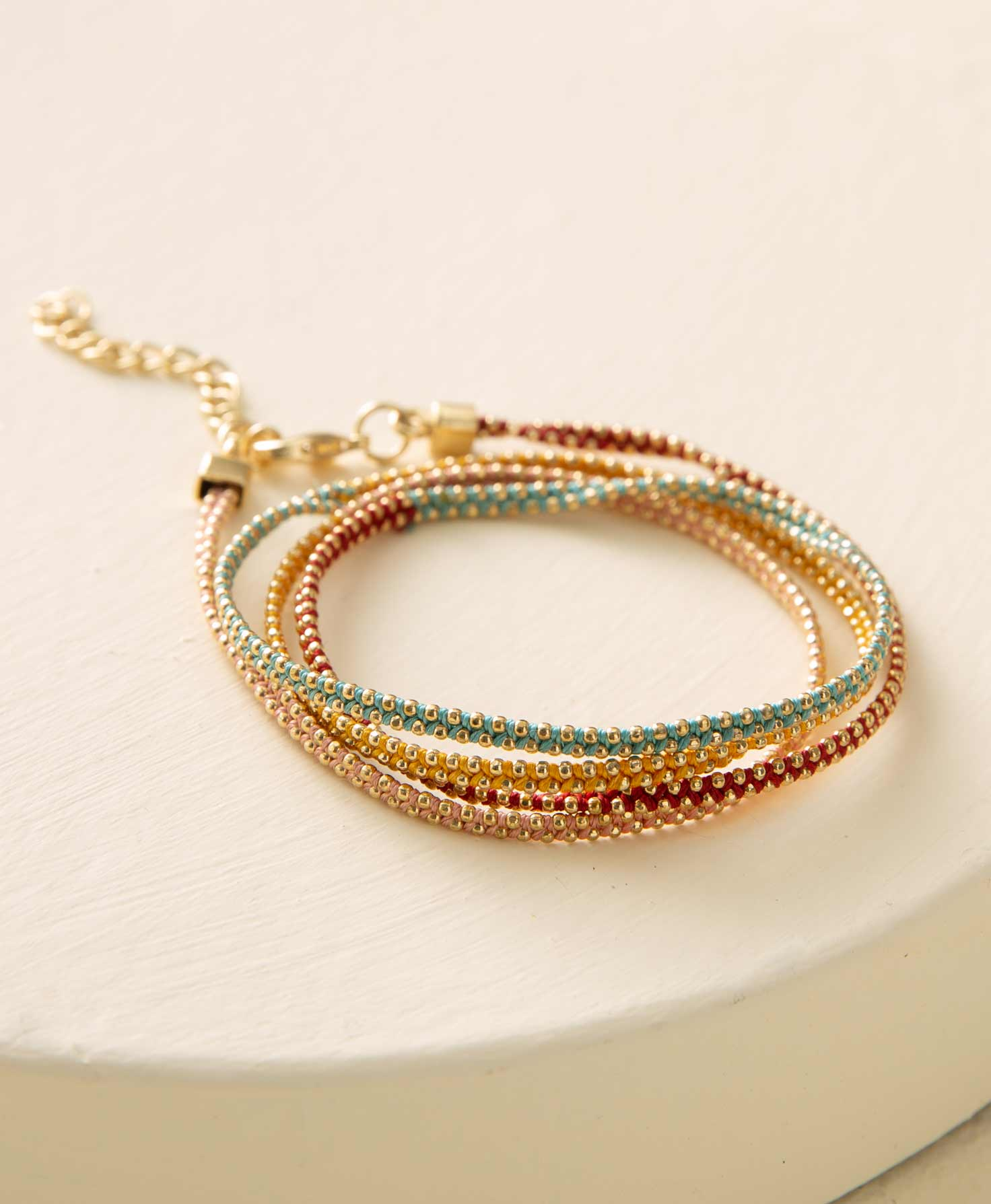 The Color Blocked Wrap Bracelet lays coiled on a white block. It is a dainty bracelet composed of many tiny, spherical brass beads interwoven with colored thread. There is a section with yellow thread, then a section with aqua thread, then a section with crimson thread. The bracelet ends in a golden chain with an extender for adjusting length.