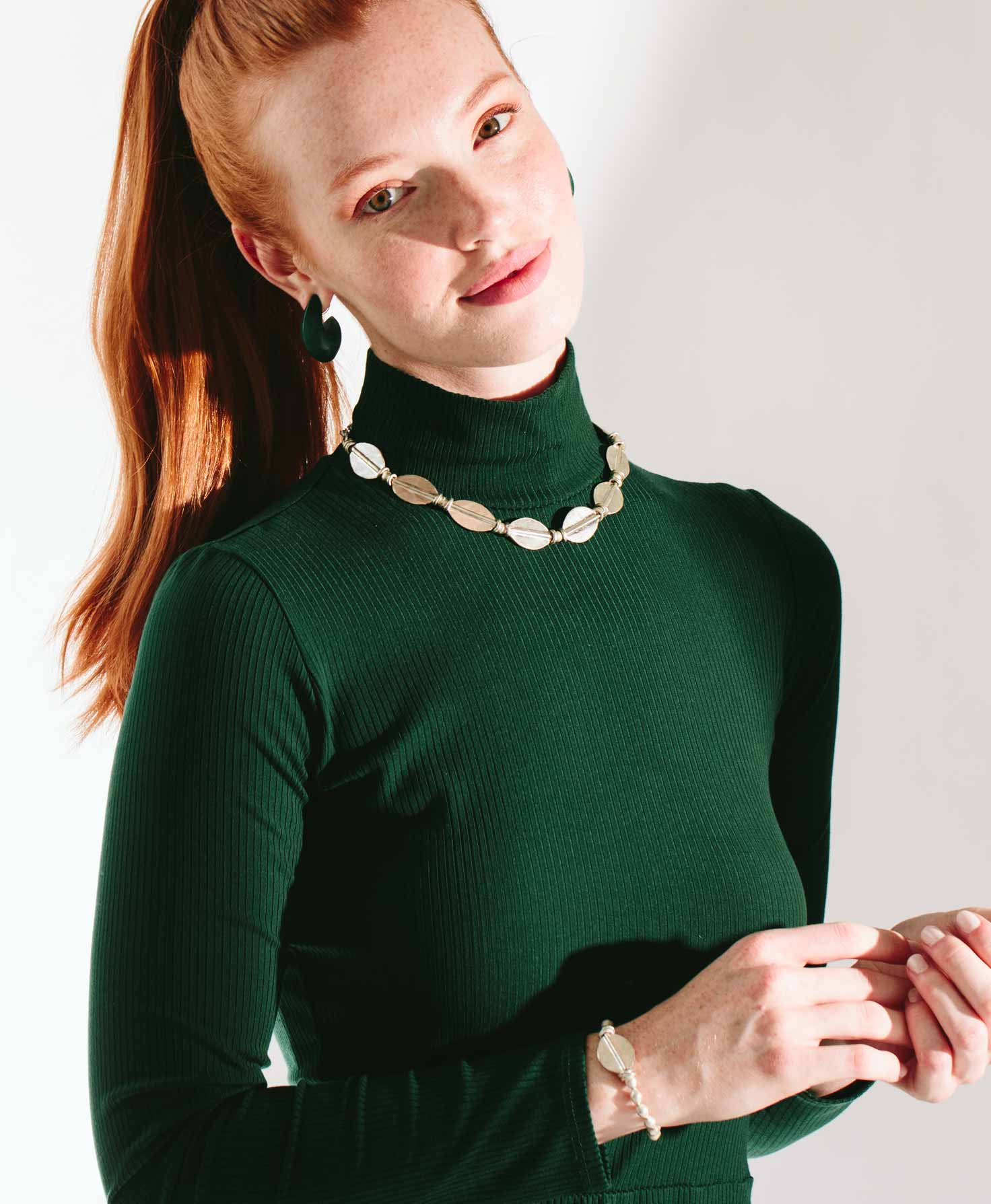 A model wears the Comrade Bracelet paired with a deep emerald green top. She also wears a silver necklace that mirrors the shade of the bracelet. The bright silver jewelry stands out against the dark top.