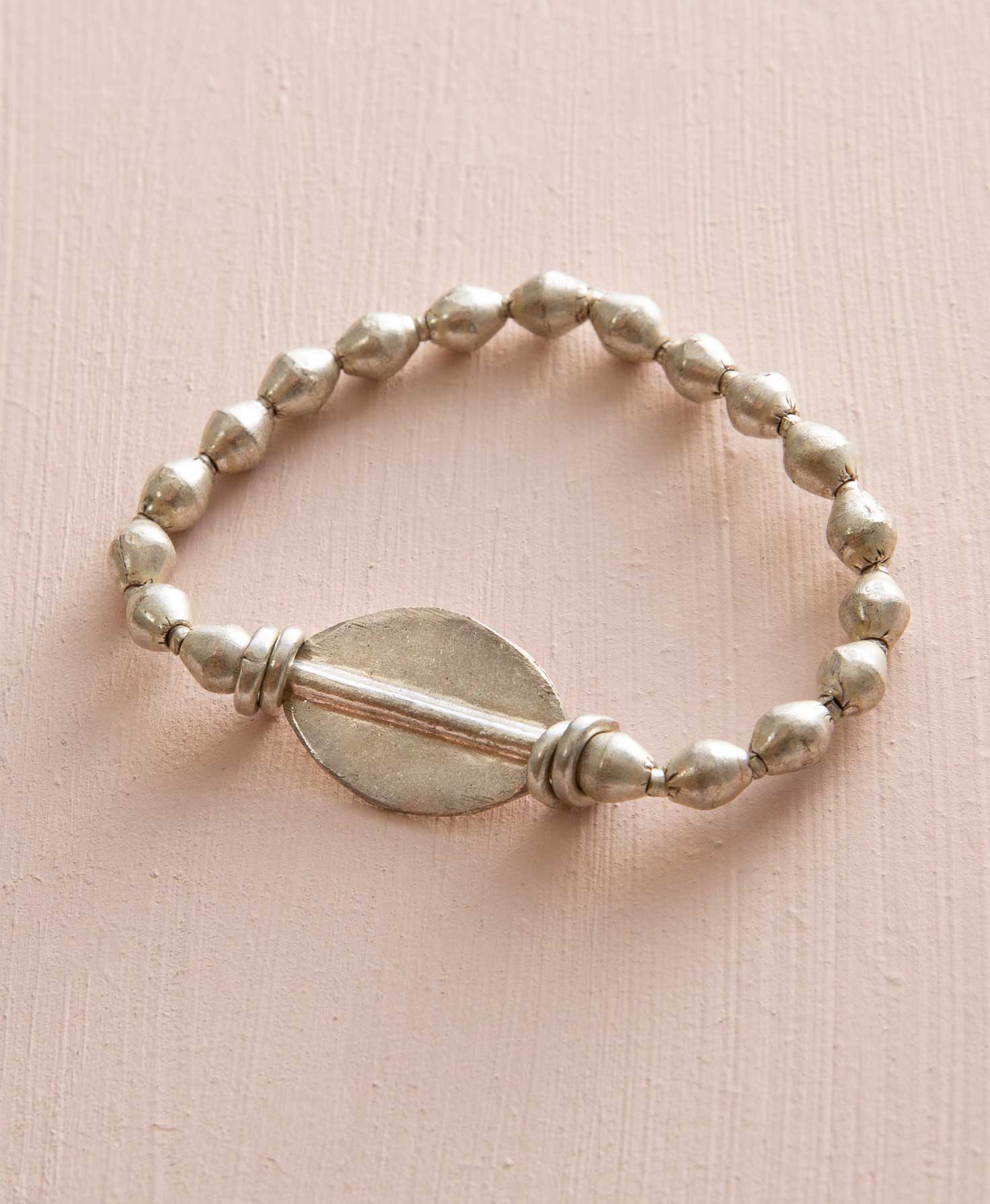 The Comrade Bracelet lies on a cream background. It is a stretchy bracelet strung with silver beads formed from upcycled artillery and mixed metal. The beads are widest at their center, and then they taper down on either side. At the center of the bracelet is a larger silver piece. It is flat and shaped like a rounded diamond, similar to the small beads but on a larger scale. A silver bar runs horizontally through its center.