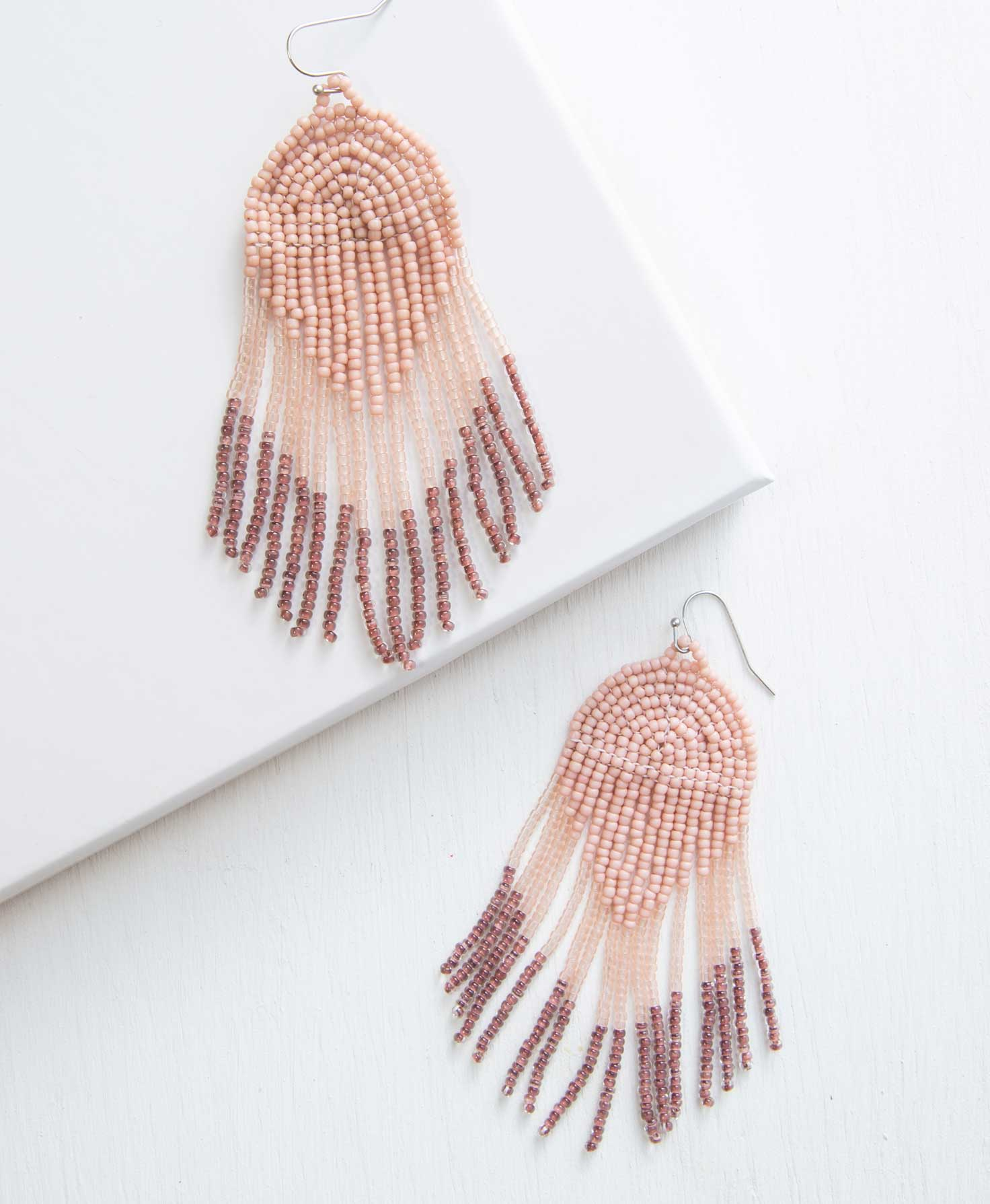 The Crux Earrings lay on a white background. They are boho-style, beaded chandelier earrings. They feature silver ear hooks with glass beads in three different shades hanging down. The top of the design is composed of blush colored beads that form an arch below the ear hook, then taper down into a V shape. Connected to this are strings of translucent blush beads that hang straight down in a fringe. The fringe ends in a line of translucent plum colored beads.