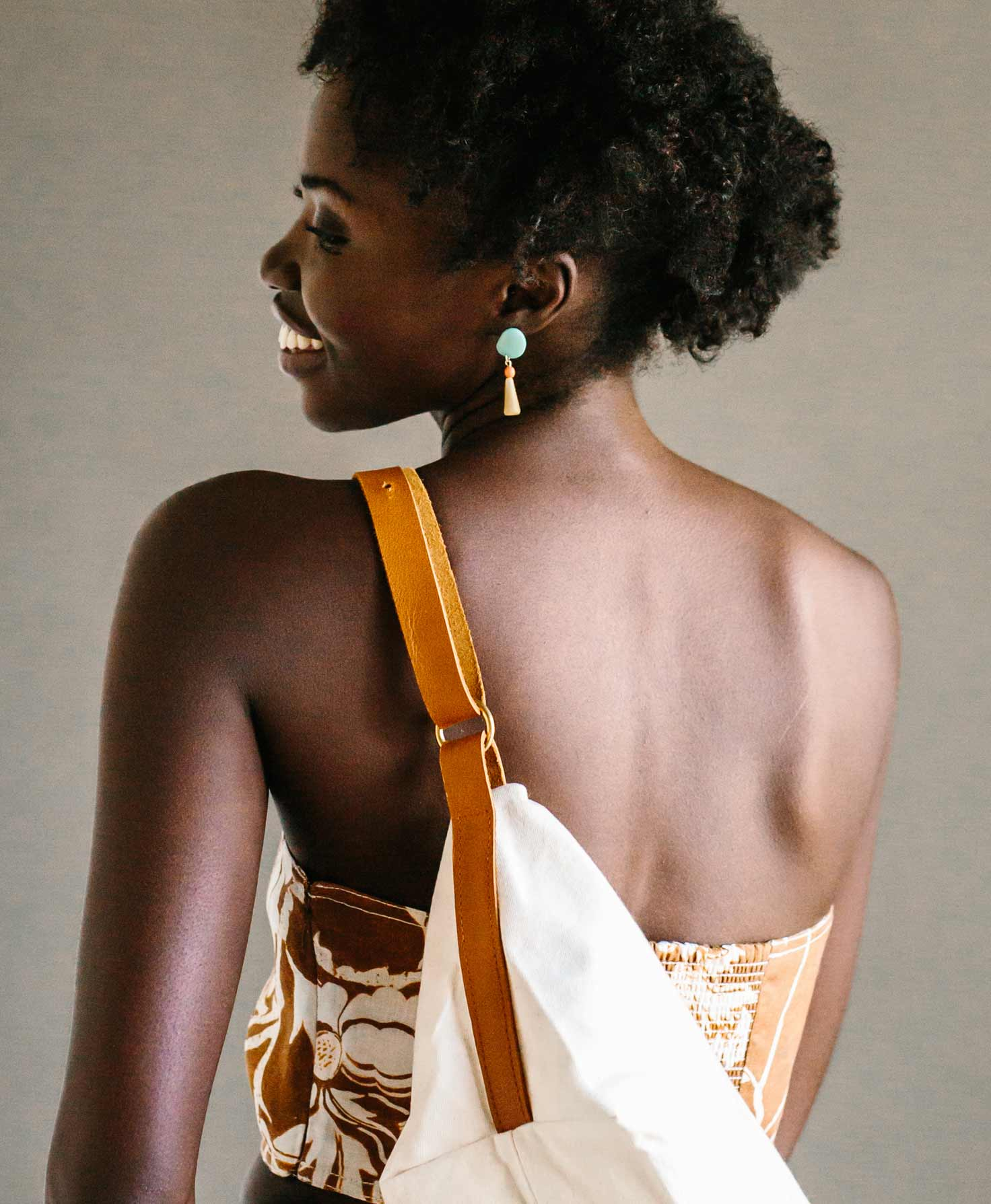 A model is shown with her back to the camera, her face turned to the side. She wears the Delphin Drop Earrings and has the Skipper Sling Bag slung over her shoulder.