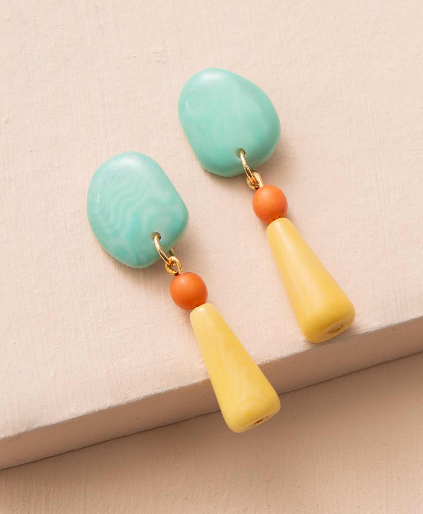 The Delphin Drop Earrings lay on a peach background. They are stud-style earrings with dangling pieces hanging down. The pieces are made of polished tagua seed that has been dyed. Affixed to the stud is a round aqua tagua piece with a natural, slightly irregular shape. There is a jump ring below this that attaches to a small, bright orange tagua bead. Below this is a long yellow tagua piece that starts narrow and widens slightly toward the bottom.