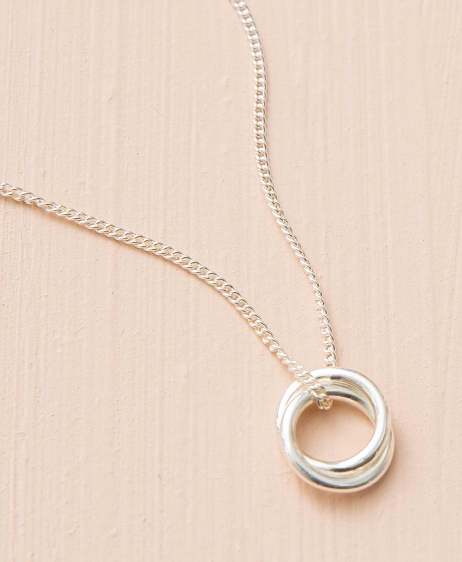 The Demi Knot Necklace lays on a peach background. It is a dainty necklace with a classic feel. Two interlocking circles formed from smooth sterling silver hang on a silver chain.