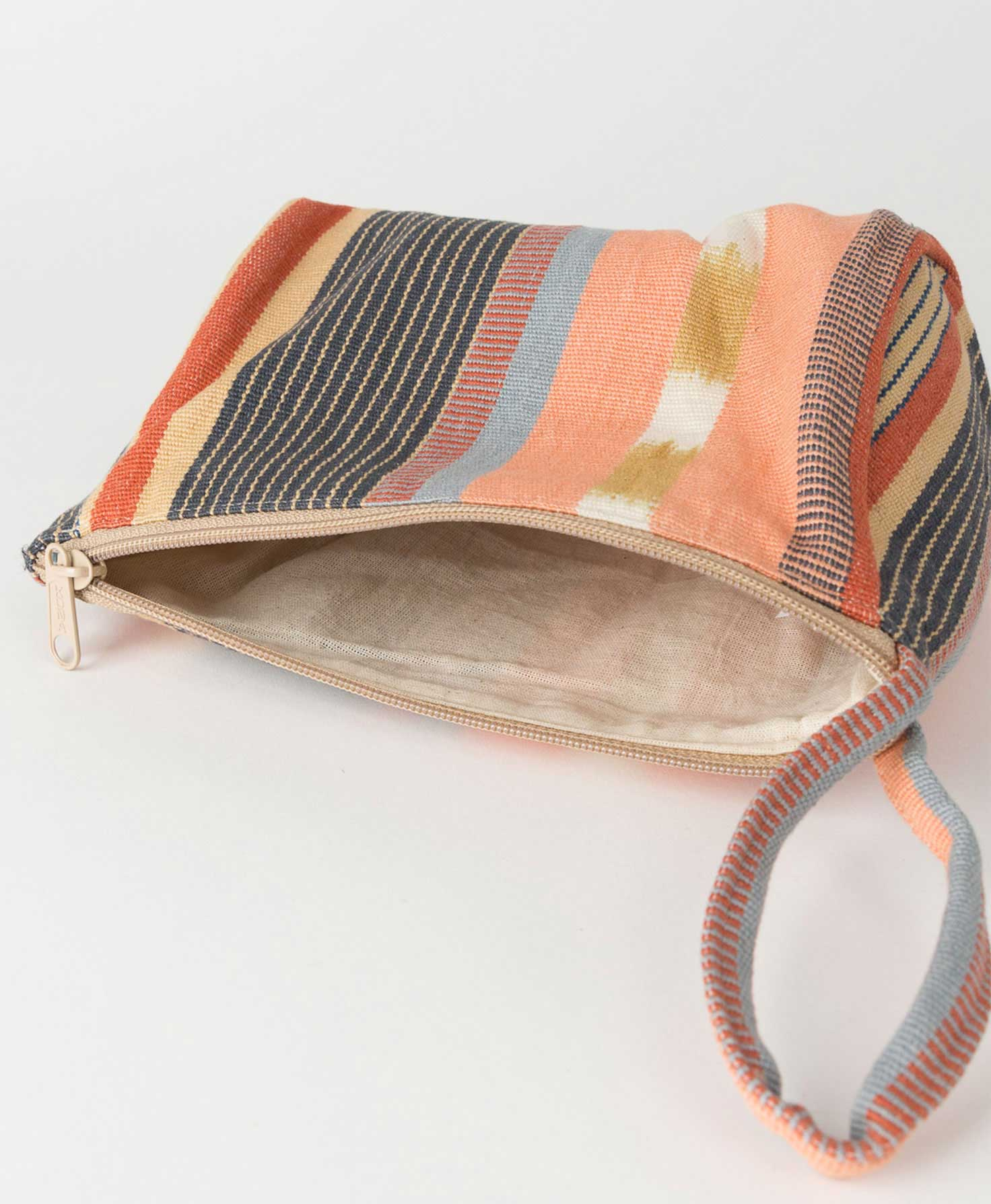 The Drifter Makeup Bag lays on its side with its zipper open. The interior is a solid, sand-colored fabric with a handwoven look.