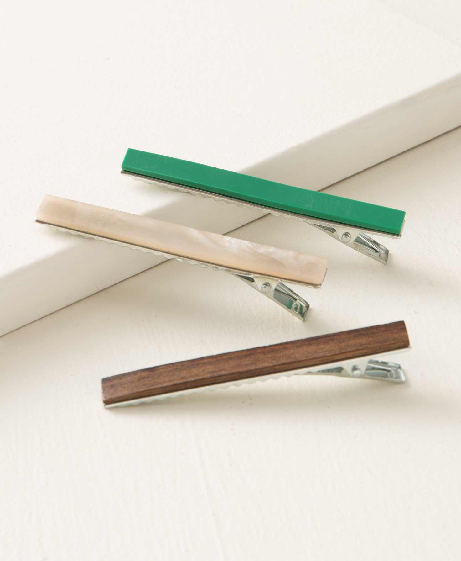 The three hair clips included in the Earth Tone Hair Clips set rest on a white block. The clip hardware is silver metal, with long, narrow, rectangular resin pieces affixed to them. One clip features a matte, jade resin. The second features a cream resin with a pattern that resembles mother-of-pearl. The third features a dark wood grain coated in glossy resin.