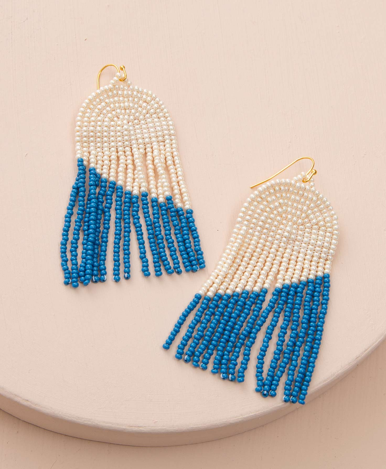 The Ensign Earrings sit on a cream-colored background. They have gold ear wires and are composed of a chandelier of glass beads. At the top of the earrings is an arch made of glossy white glass beads. Hanging from this is a fringe of cream and cobalt blue beads. Each fringe begins with cream beads, then ends in blue beads. The blue beads begin one bead later on each subsequent row of fringe, forming a design that looks like an angled line stretching down and across the fringe.