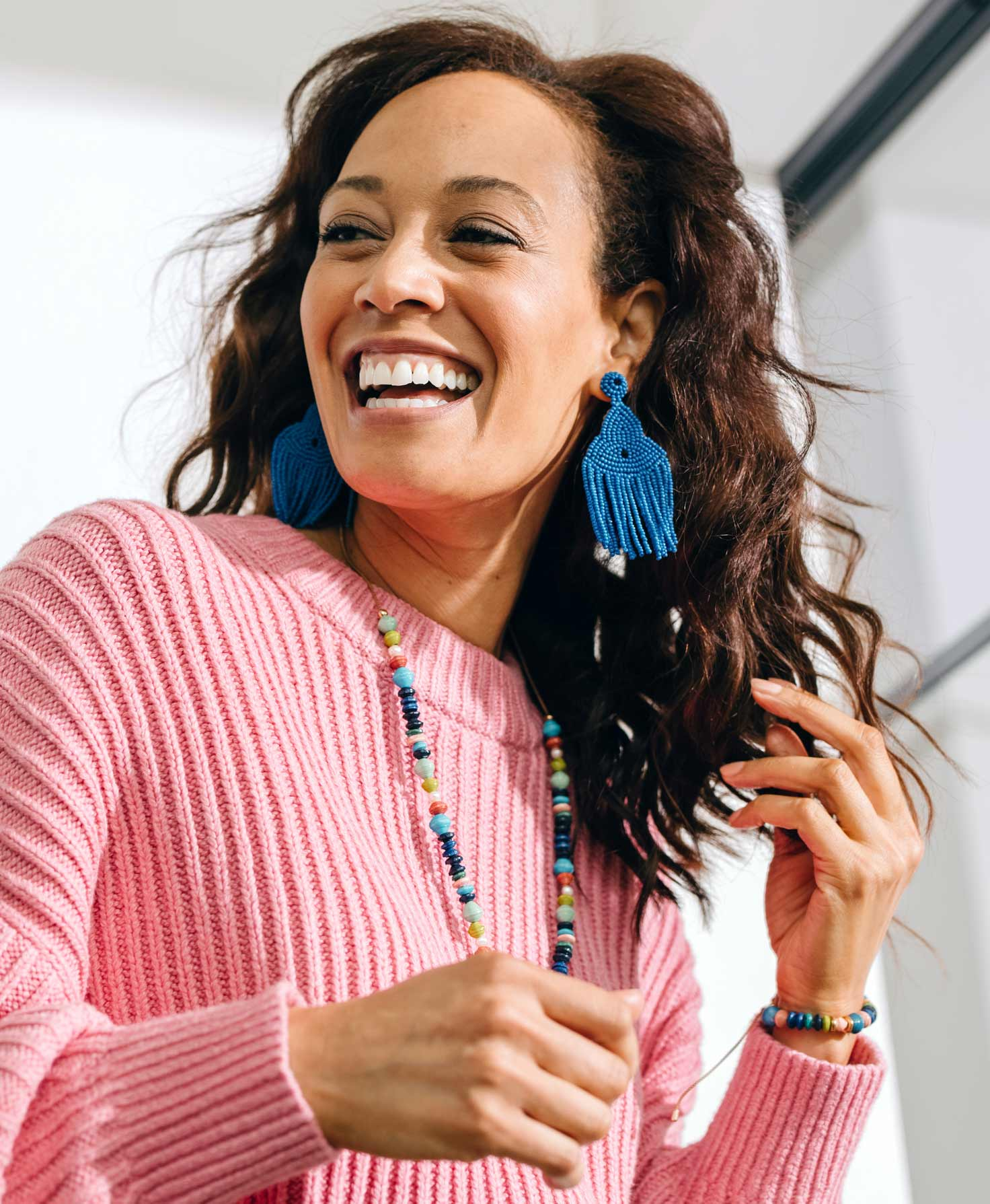 A model wears the Enthusiast Earrings, which hang down and move freely as she turns. She also wears the Bevy Bracelet and True Colors Necklace, which feature shades of blue that pair well with the earrings.