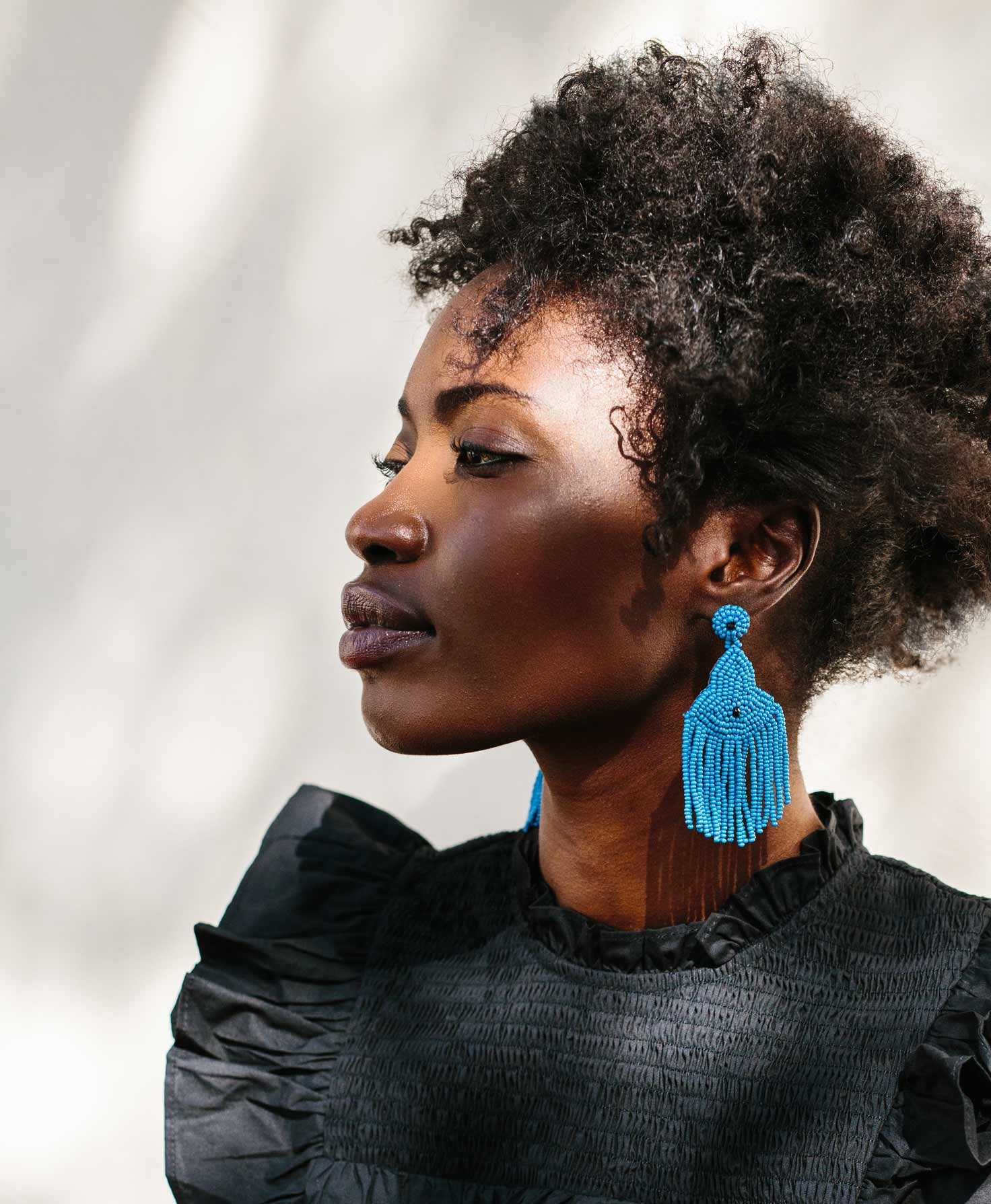 A model wears the Enthusiast Earrings, which shine in the sunlight. She wears a frilly black top, creating a strong contrast with the bright blue earrings.