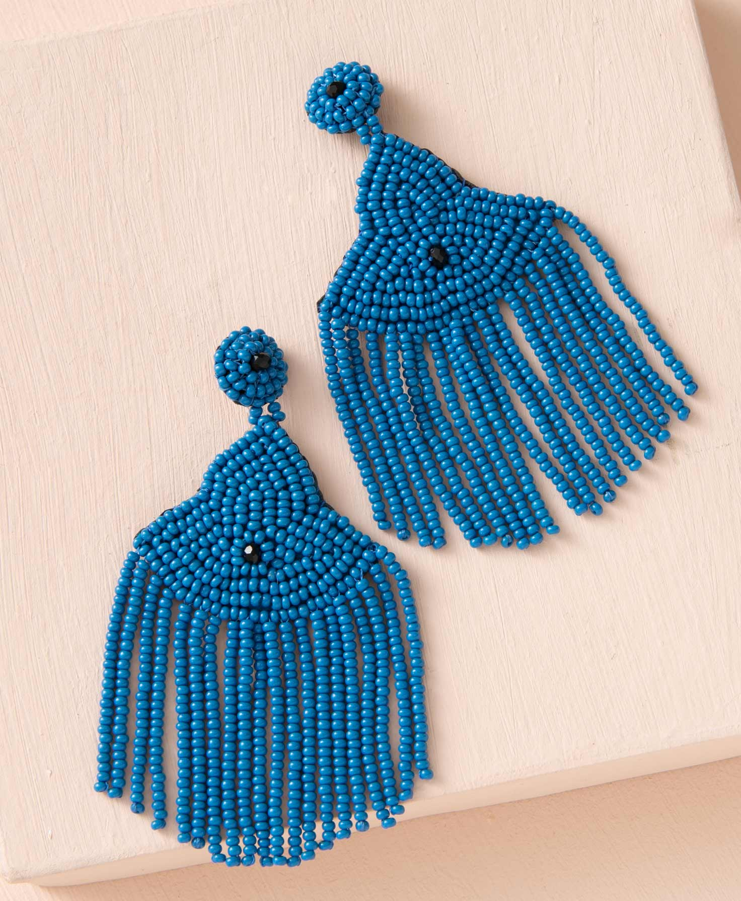 The Enthusiast Earrings lay on a peach background. They are post-style earrings with a chandelier of blue glass beads hanging down. The post itself is covered in these blue beads, with a single black, faceted glass bead in the center that adds a hint of glimmer. Connected to the post, a structured pattern of blue beads tapers down, widening as it goes to form a shape that roughly resembles an eye. In the center is another faceted black bead. Below this shape, many strands of blue beads hang down to form a fringe.